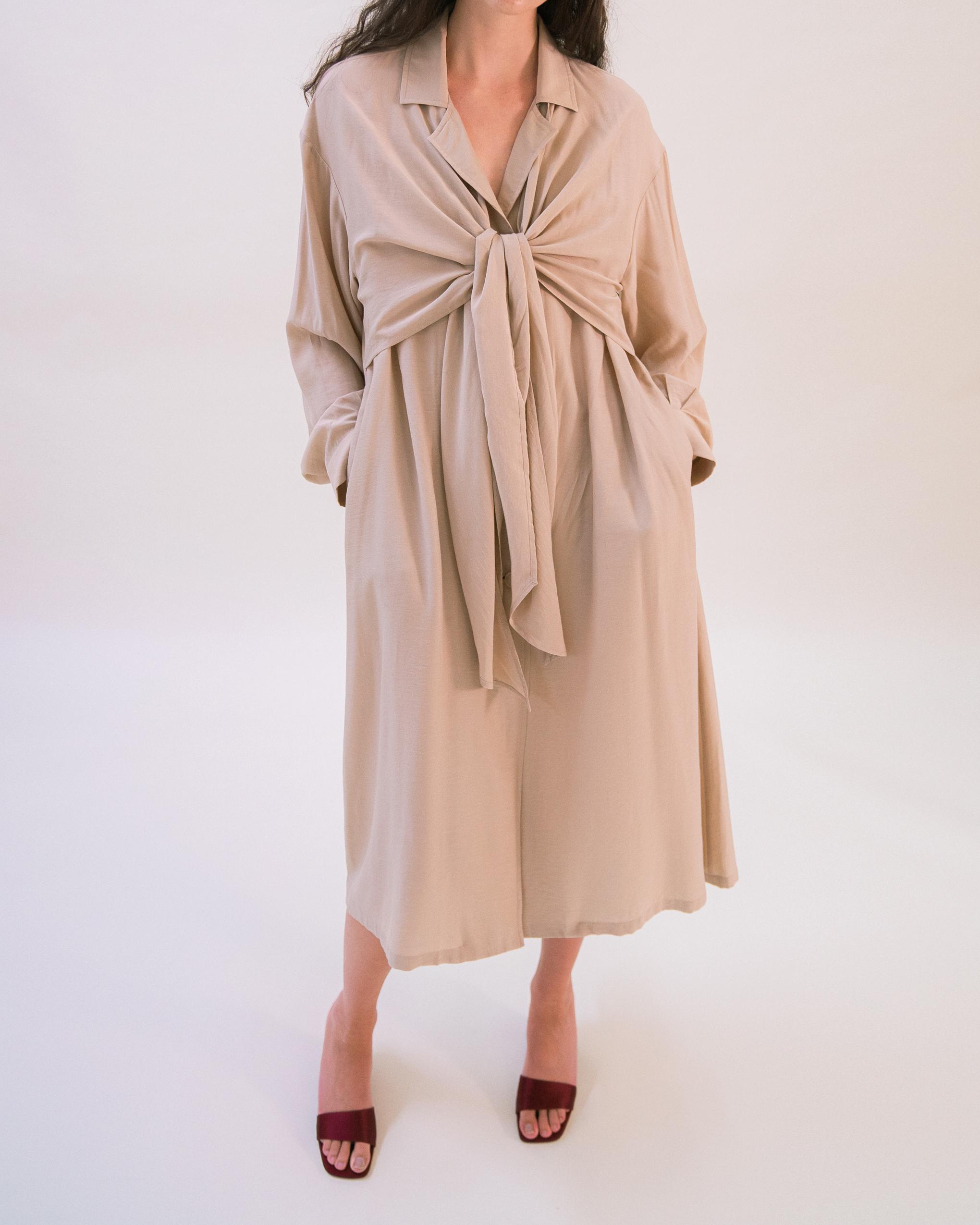 A women is wearing a beige tie front trench coat.