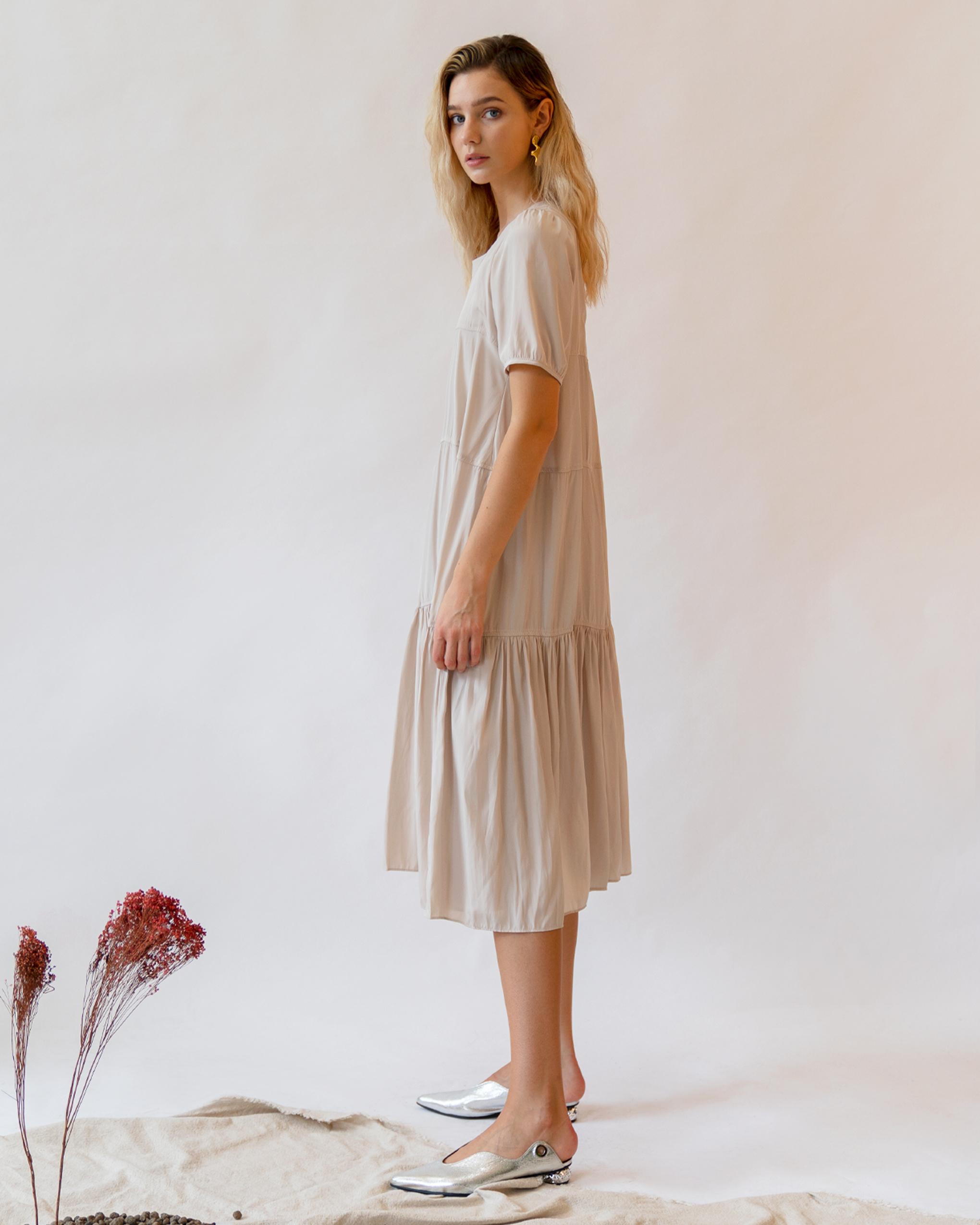 A women is wearing beige tiered smock dress.