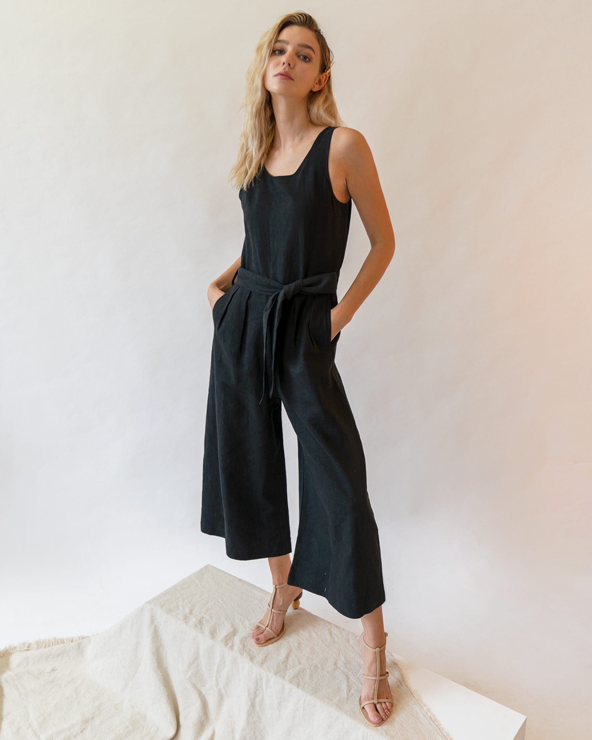 A woman is wearing a black sleeveless scoop back linen jumpsuit.