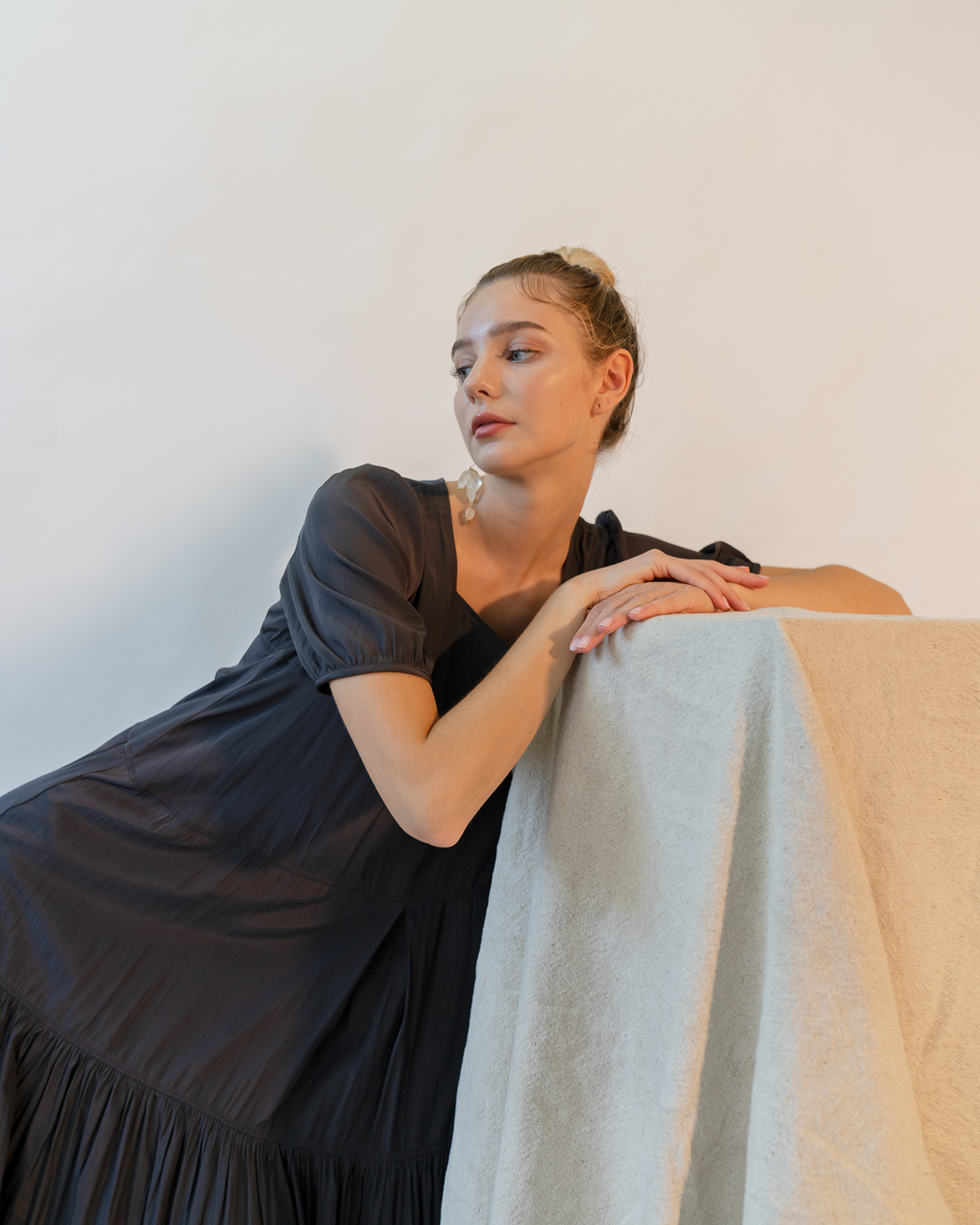 A woman is wearing a black tiered smock dress.