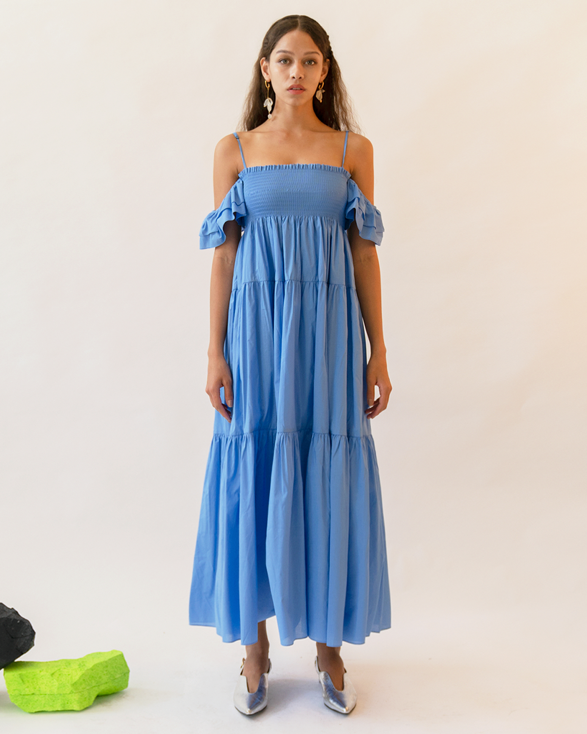 A woman is wearing a blue ruffle off-the-shoulder dress.