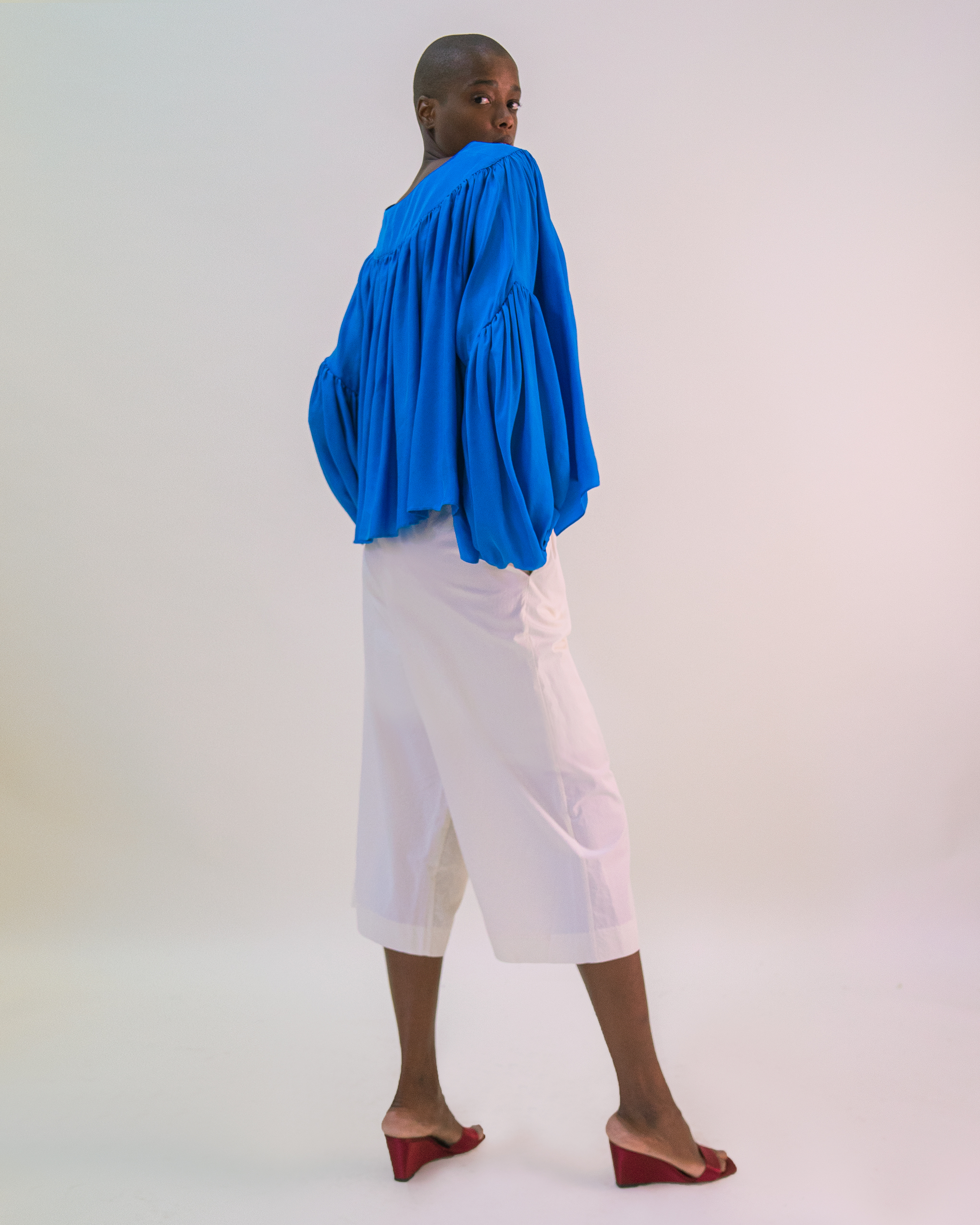 A women is wearing cobalt blue volume blouse and white cotton trousers.