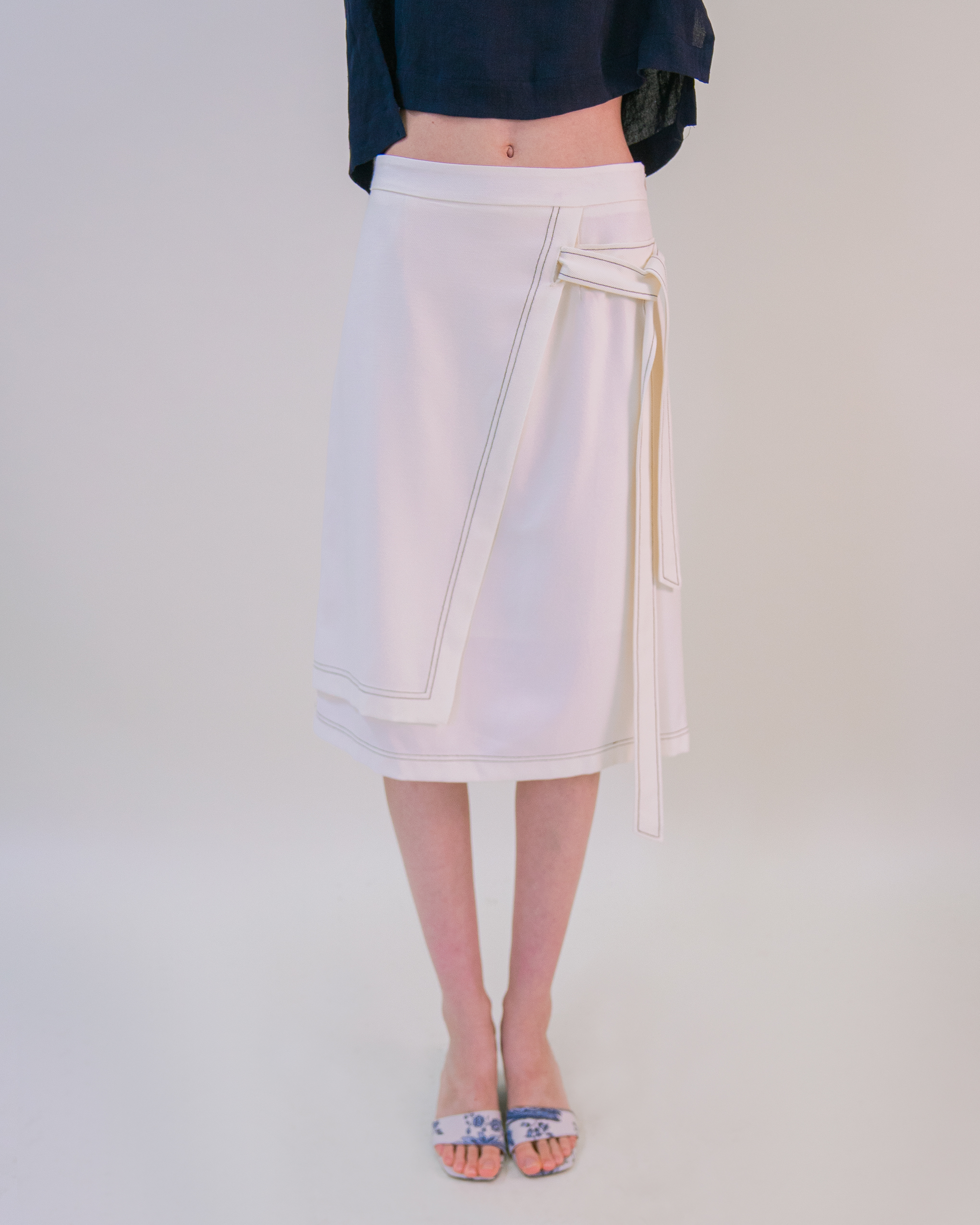 A women is wearing cream double-layer belted warp skirt.