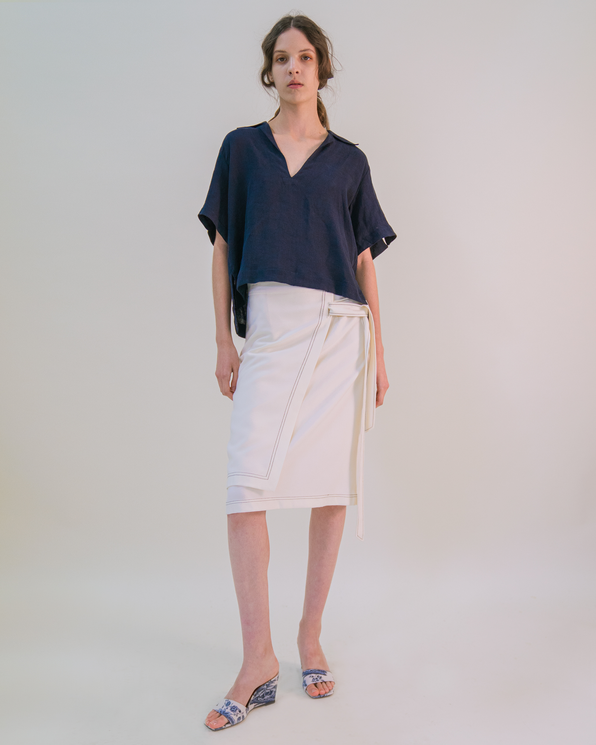A women is wearing cream double-layer belted warp skirt and short sleeve v-neck blouse.