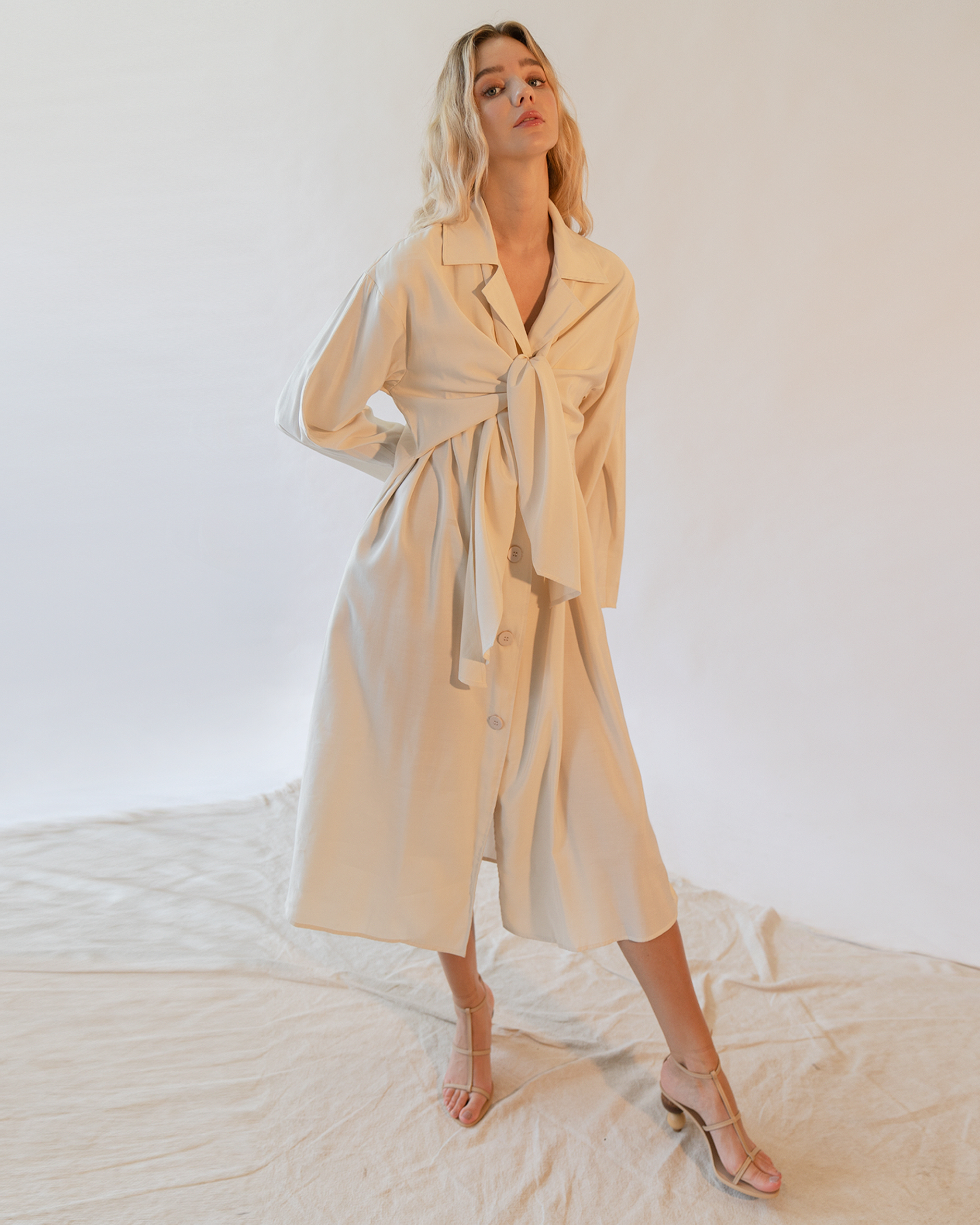 A women is wearing a cream tie front trench coat.