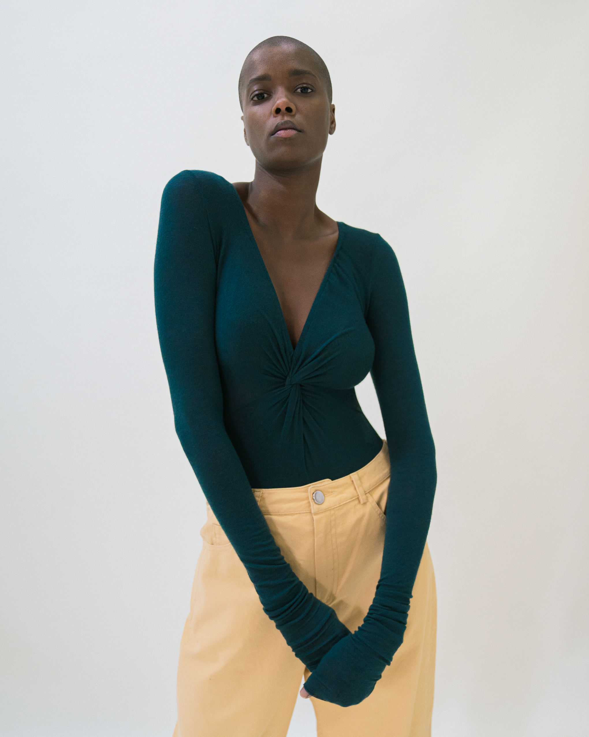 A woman is wearing teal colour front twist bodysuit and yellow trousers.