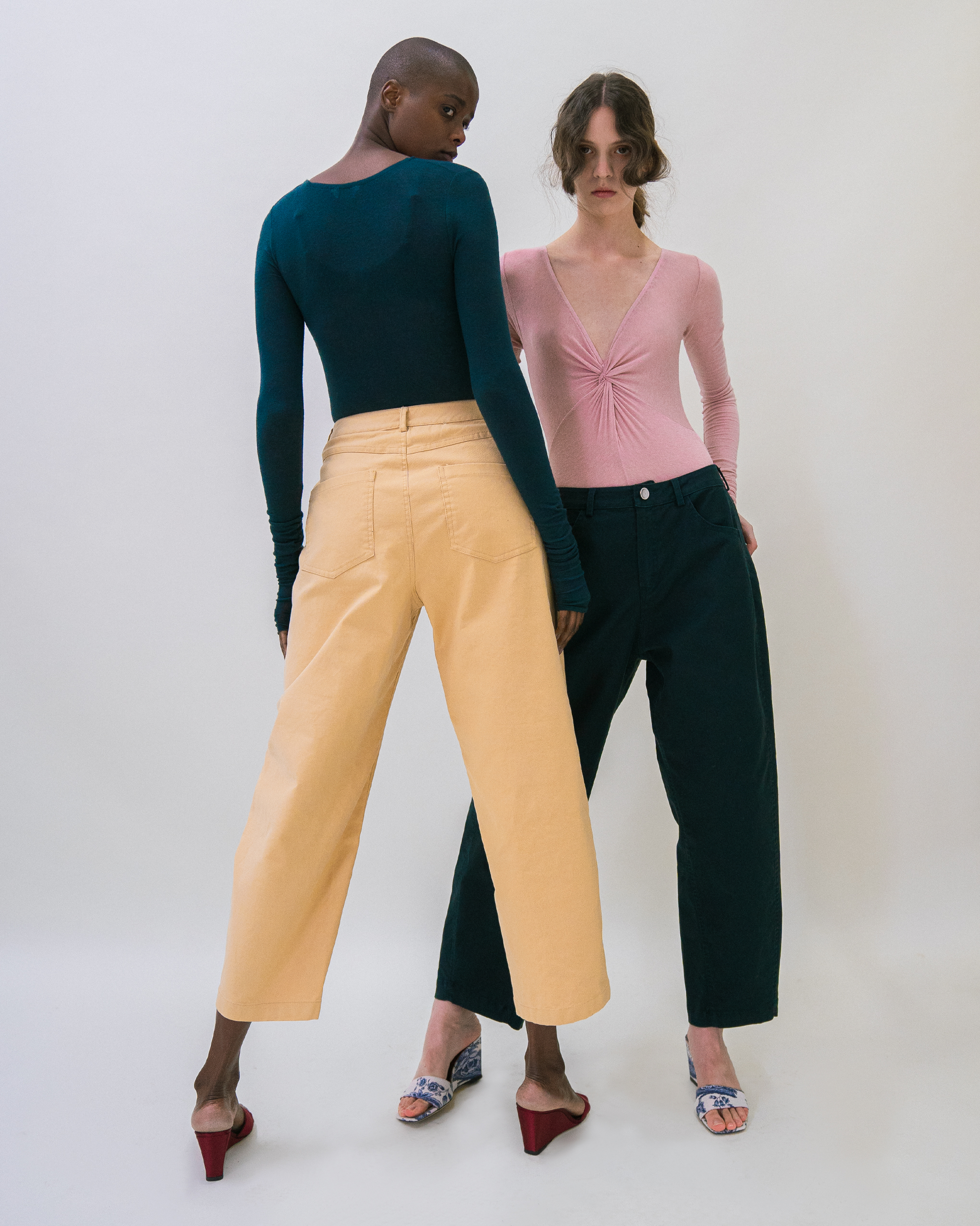 Two women are standing, one woman is wearing teal colour bodysuit and yellow trousers, the other woman is wearing pink bodysuit and teal trousers.