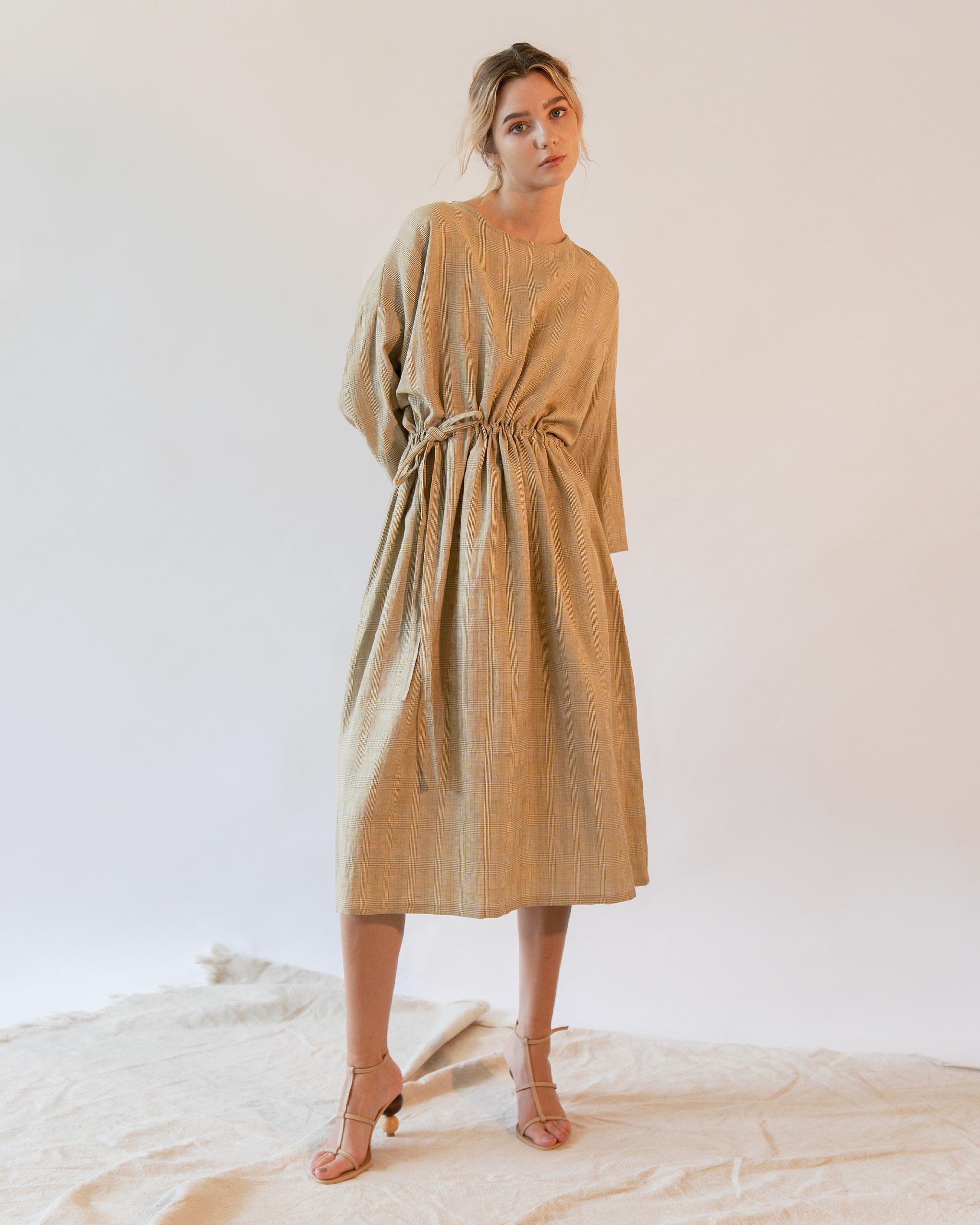 A woman is wearing yellow check pattern gathered long sleeve dress.