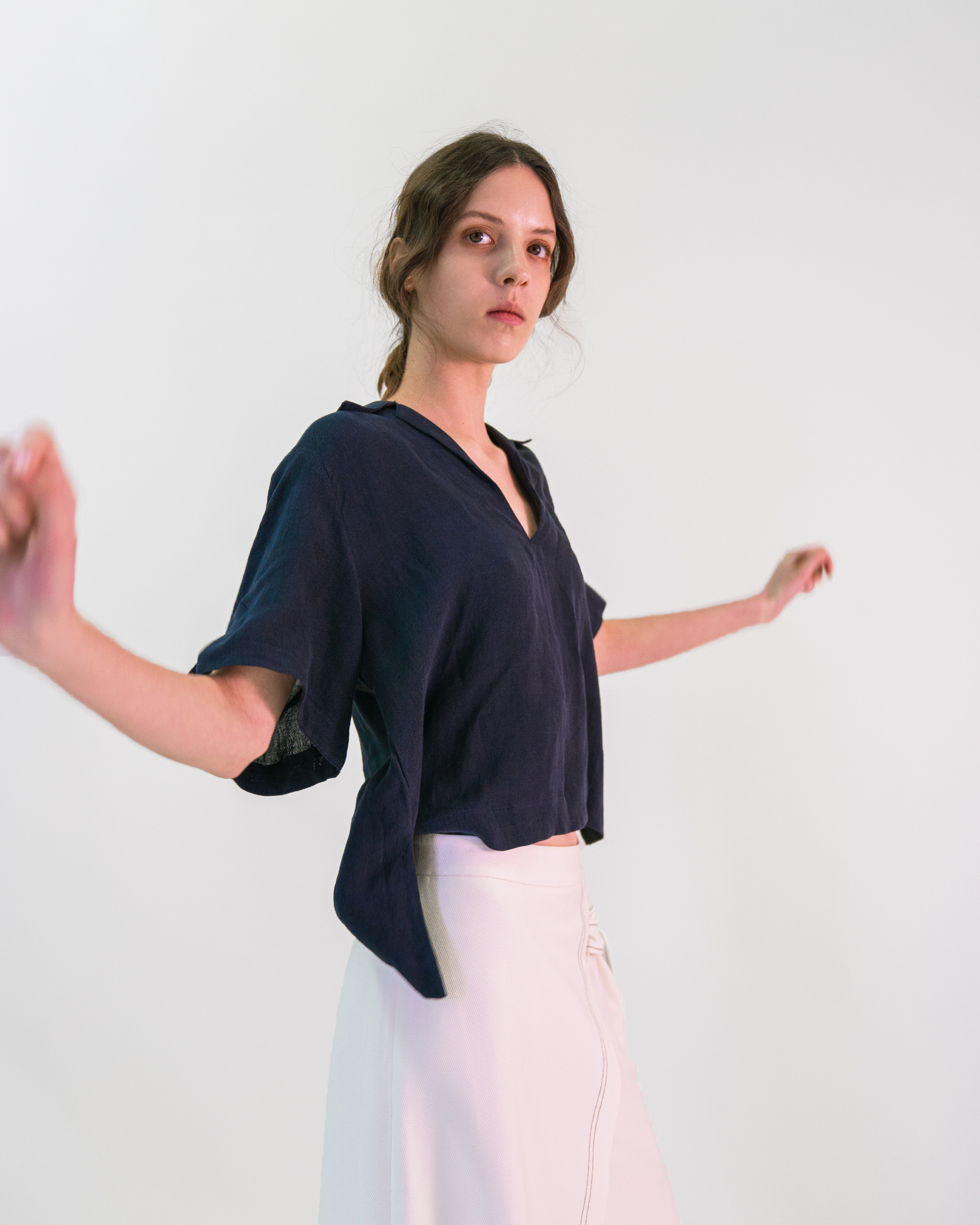 A women is wearing white contrast stitch skirt and a navy cropped pop-over linen-blend shirt blouse.