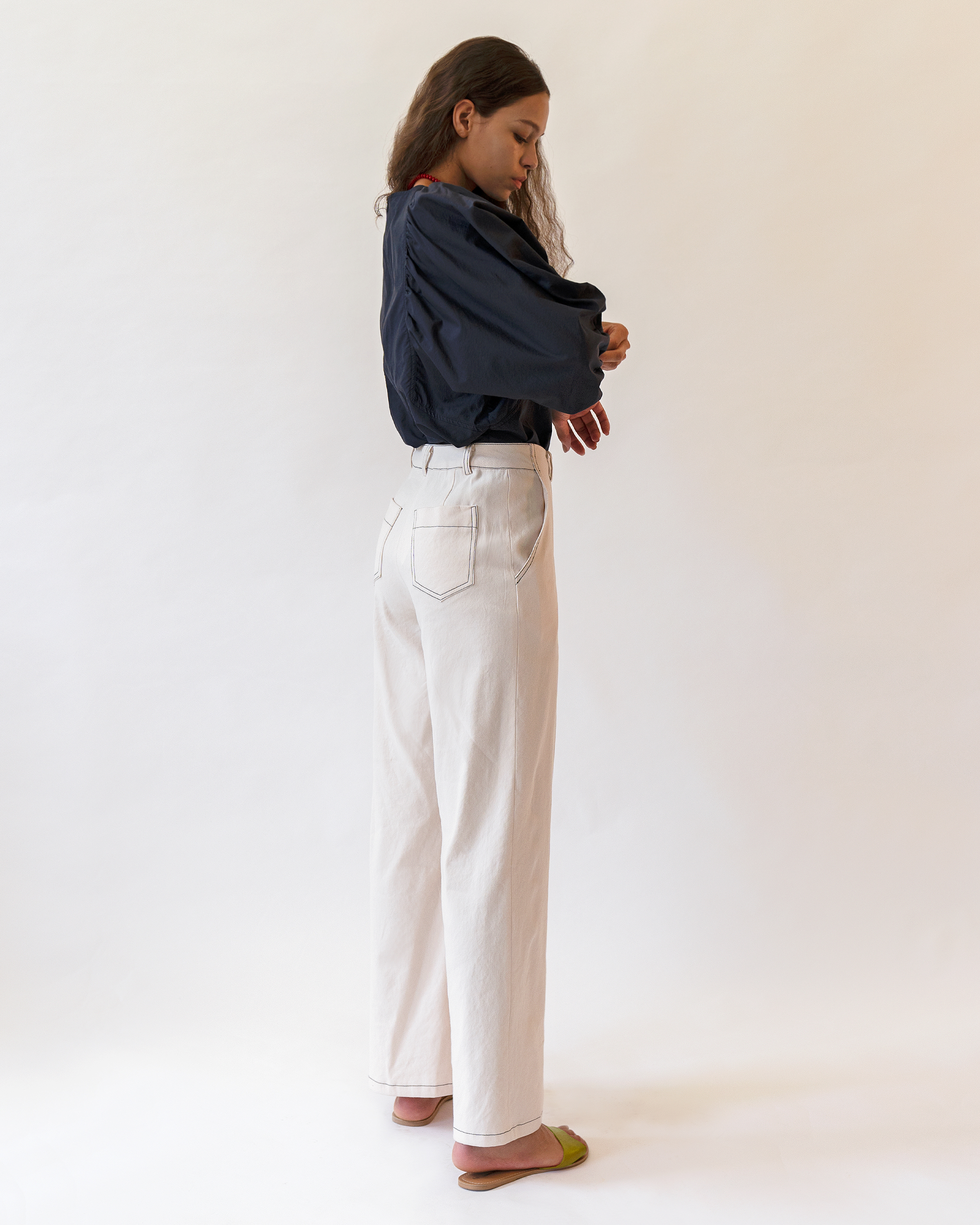 A women is wearing navy volume blouse and off white stitch trousers.