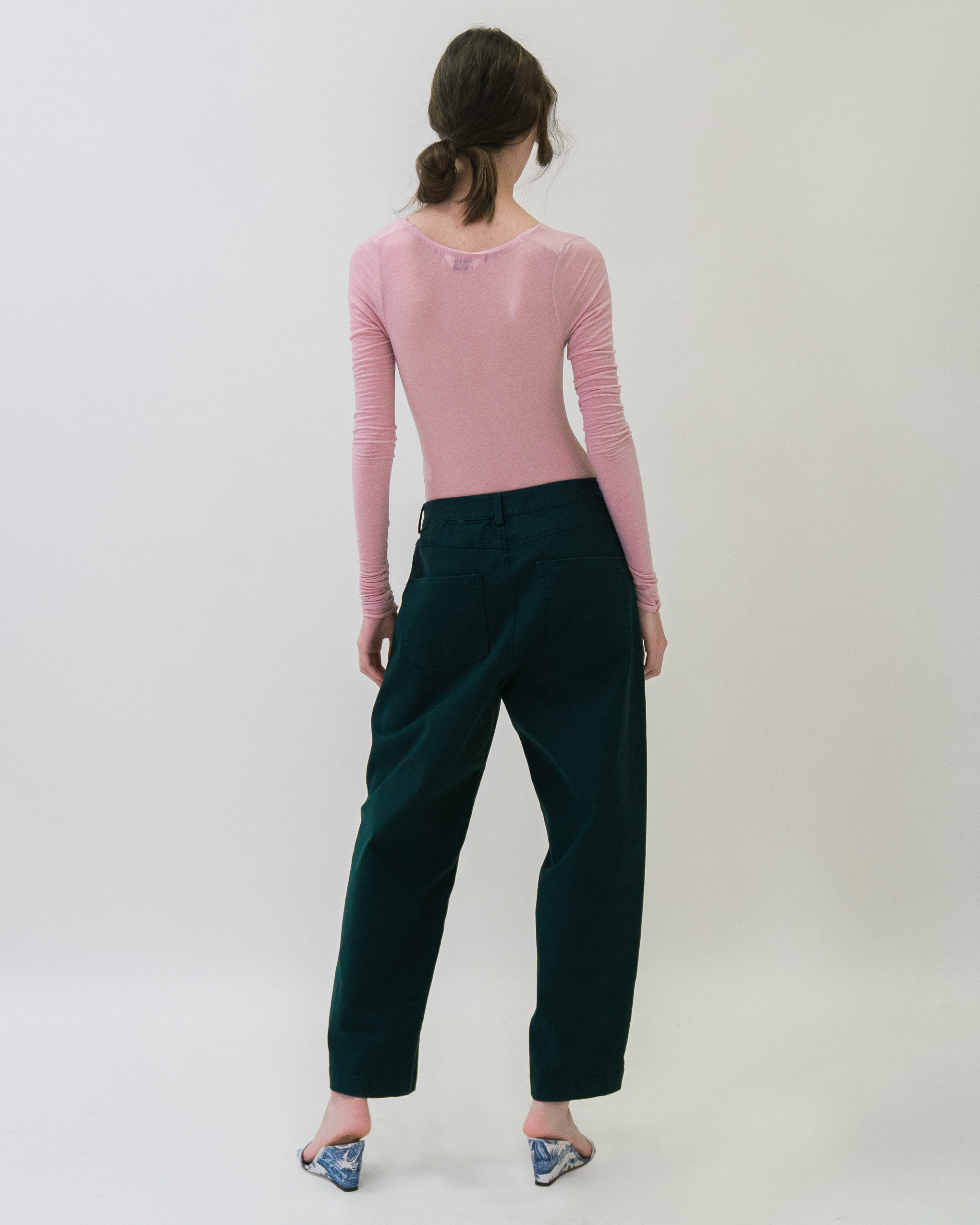 A woman is wearing pink colour front twist bodysuit and blue-green trousers.