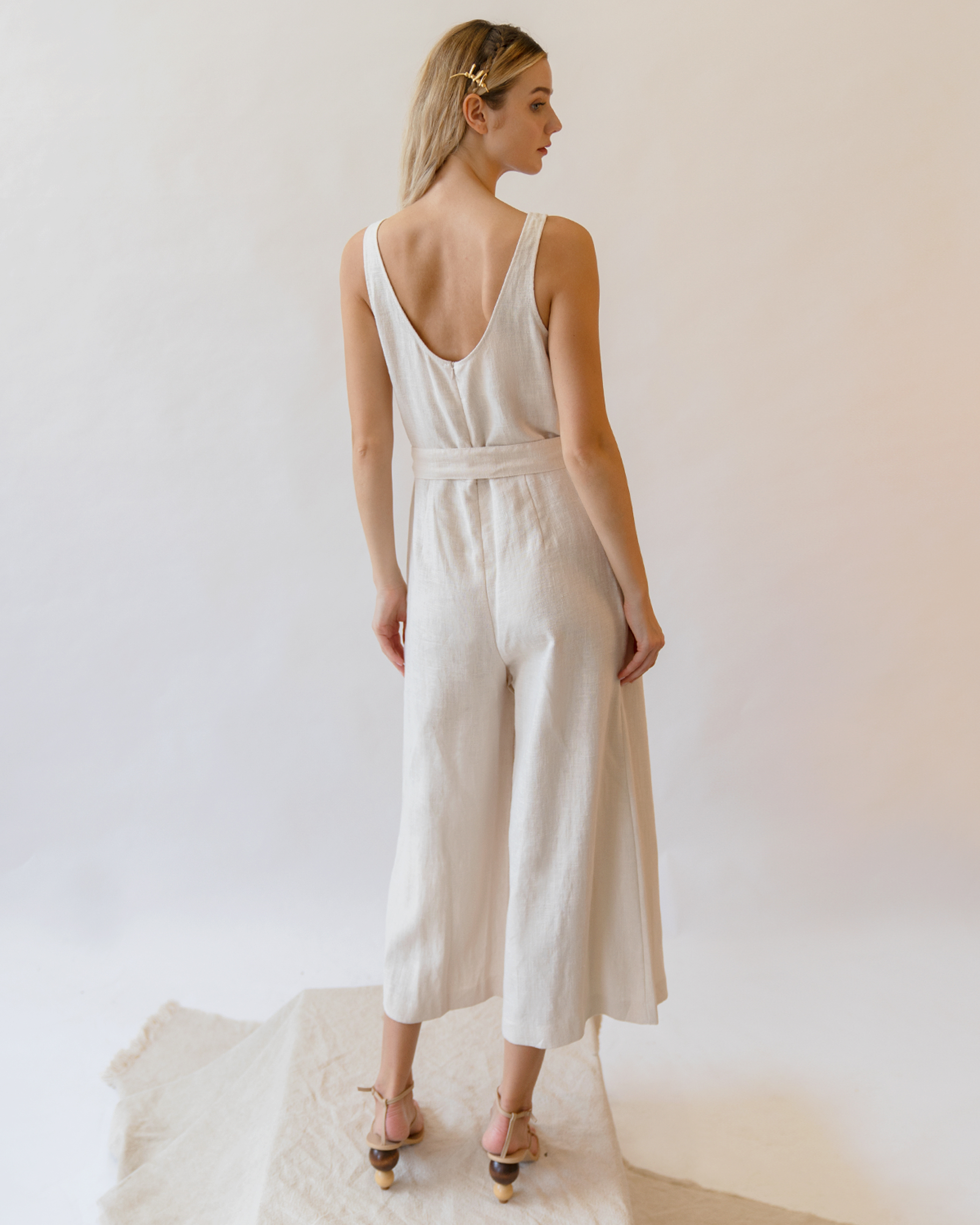 A woman is wearing a white sleeveless scoop back linen jumpsuit.