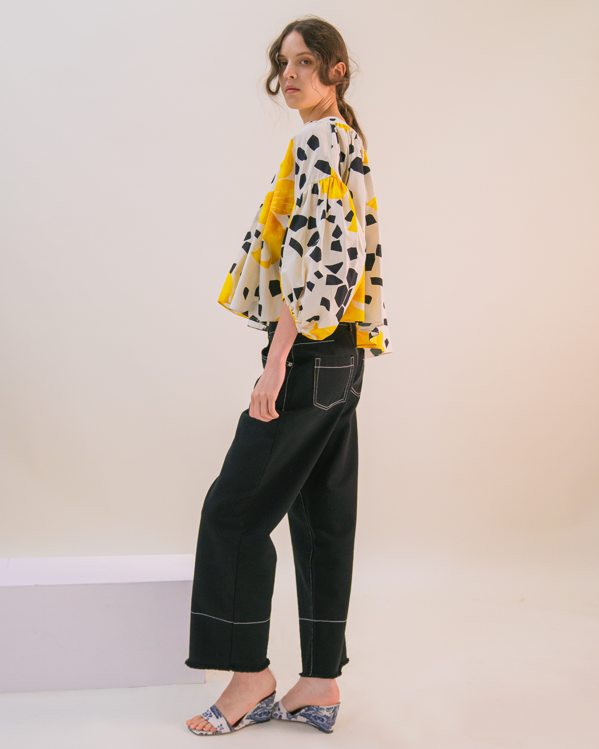 A woman is wearing yellow flower pattern volume blouse and black jeans.