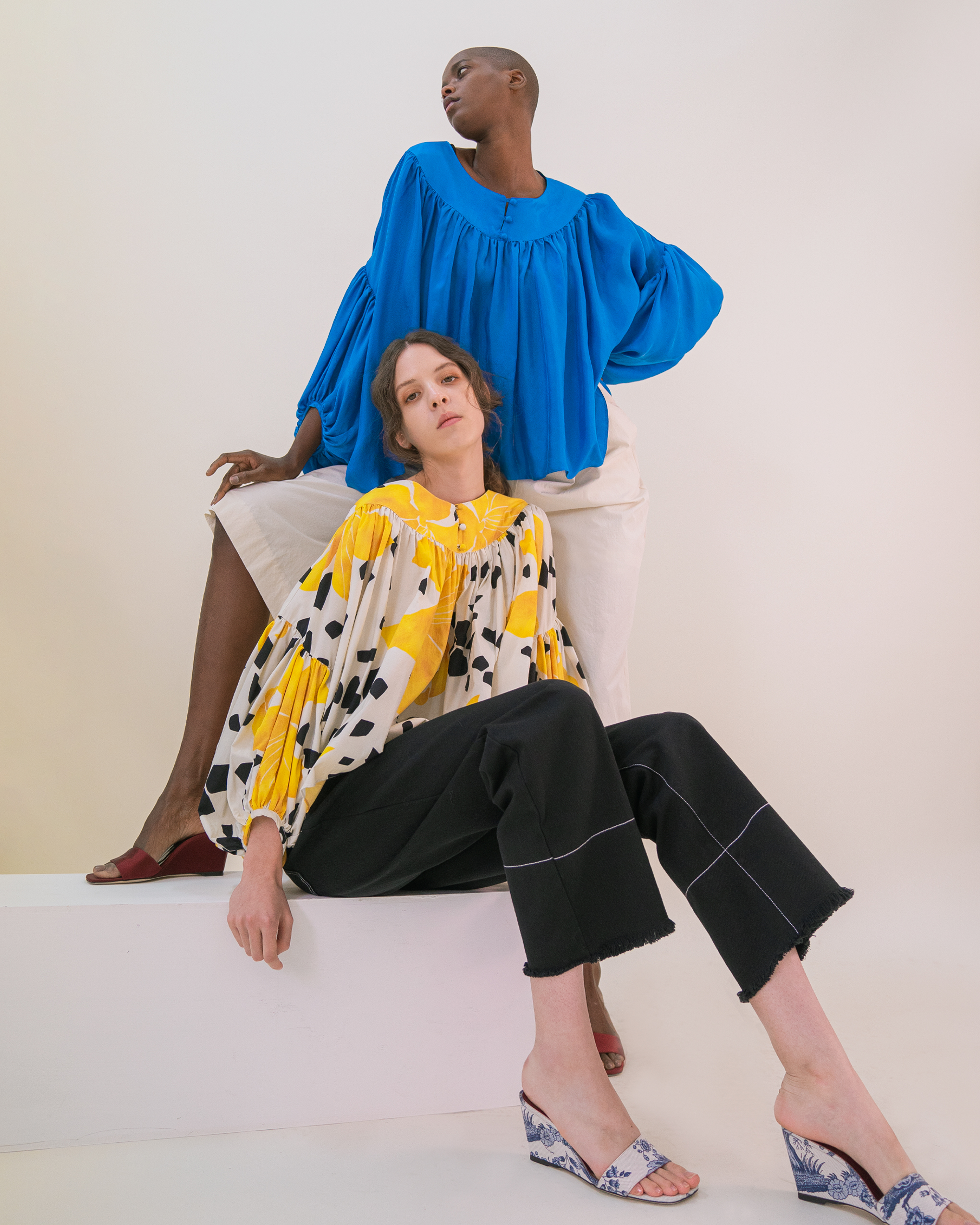 Two women are wearing volume blouses, one with yellow flower pattern and black jeans, the other one with cobalt blue and white cotton elasticated tousers.