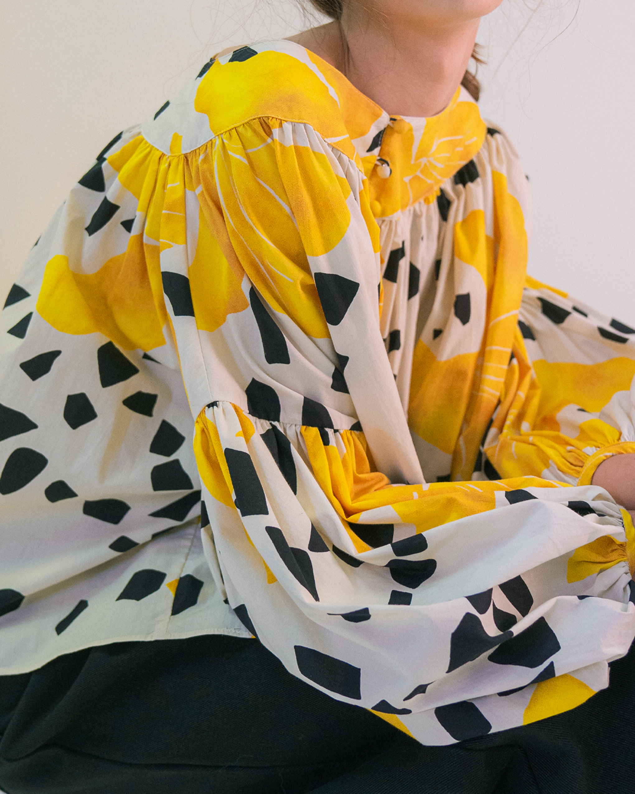 A woman is wearing yellow flower and black dot pattern blouse.