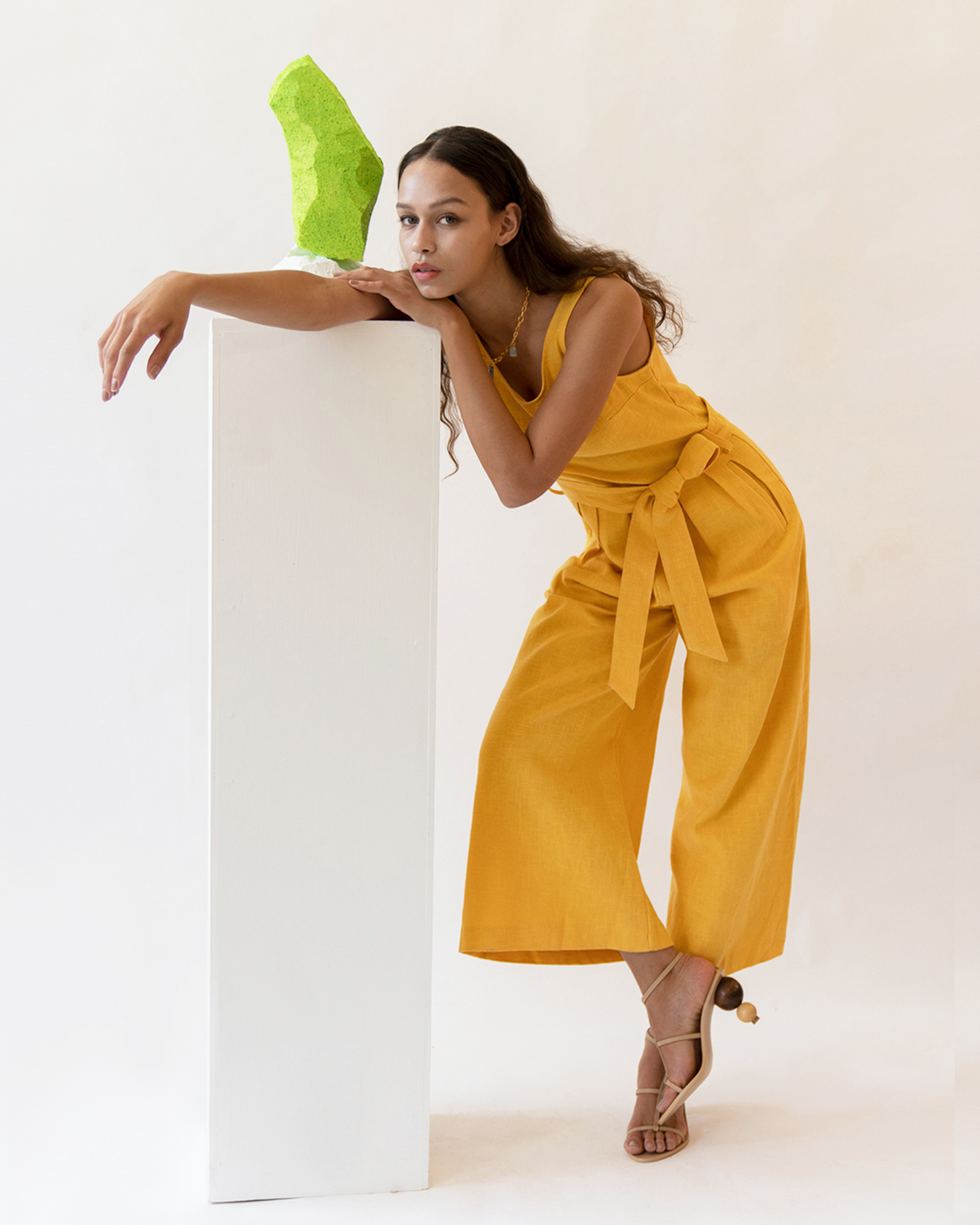 A woman is wearing a yellow sleeveless scoop back linen jumpsuit.