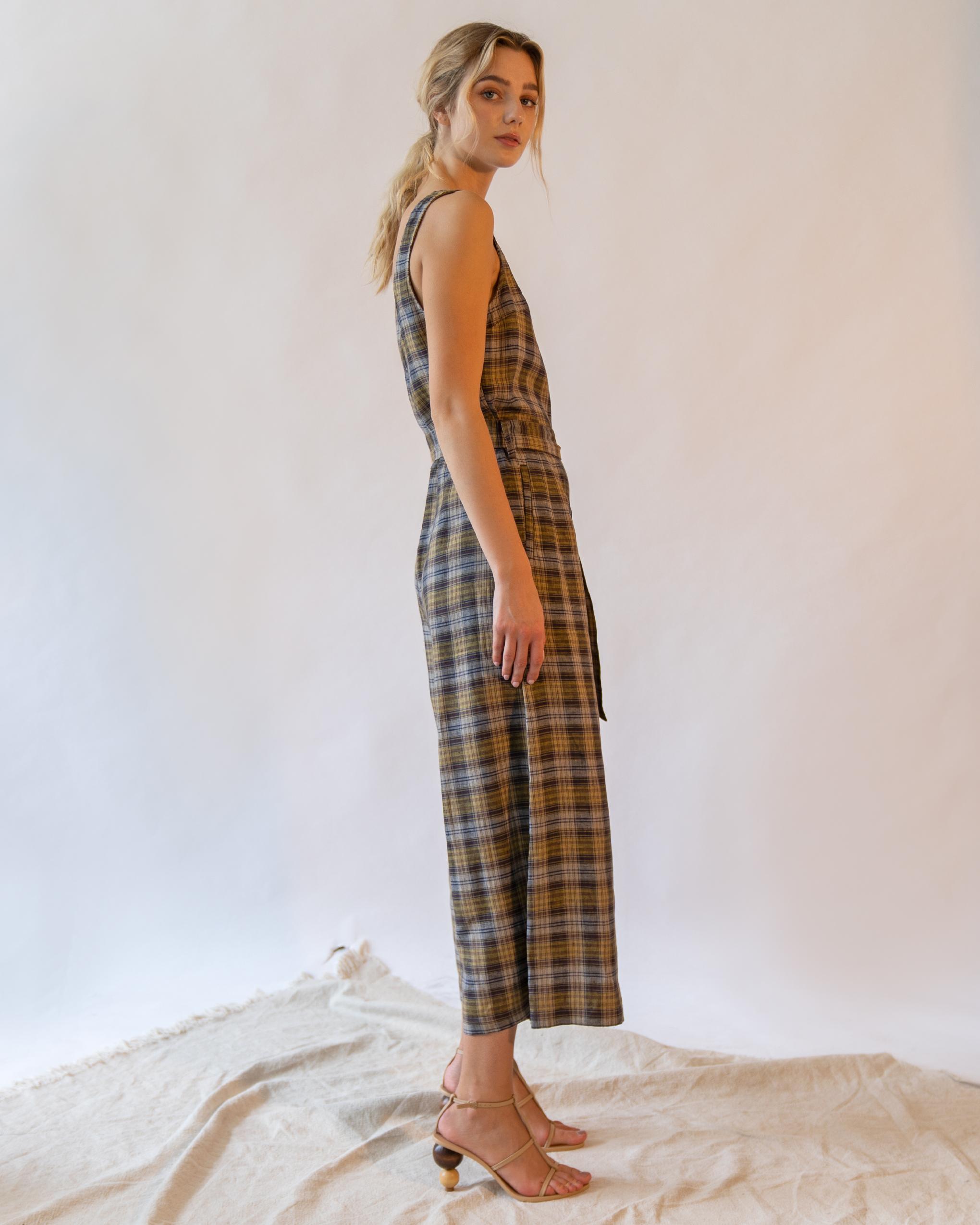 A woman is wearing beige check sleeveless scoop back linen jumpsuit.