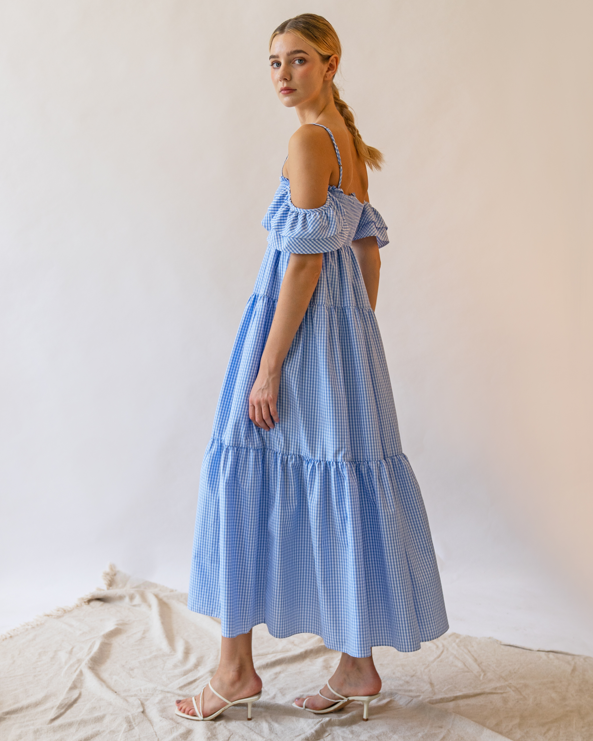 A woman is wearing a blue check ruffle off-the-shoulder dress.
