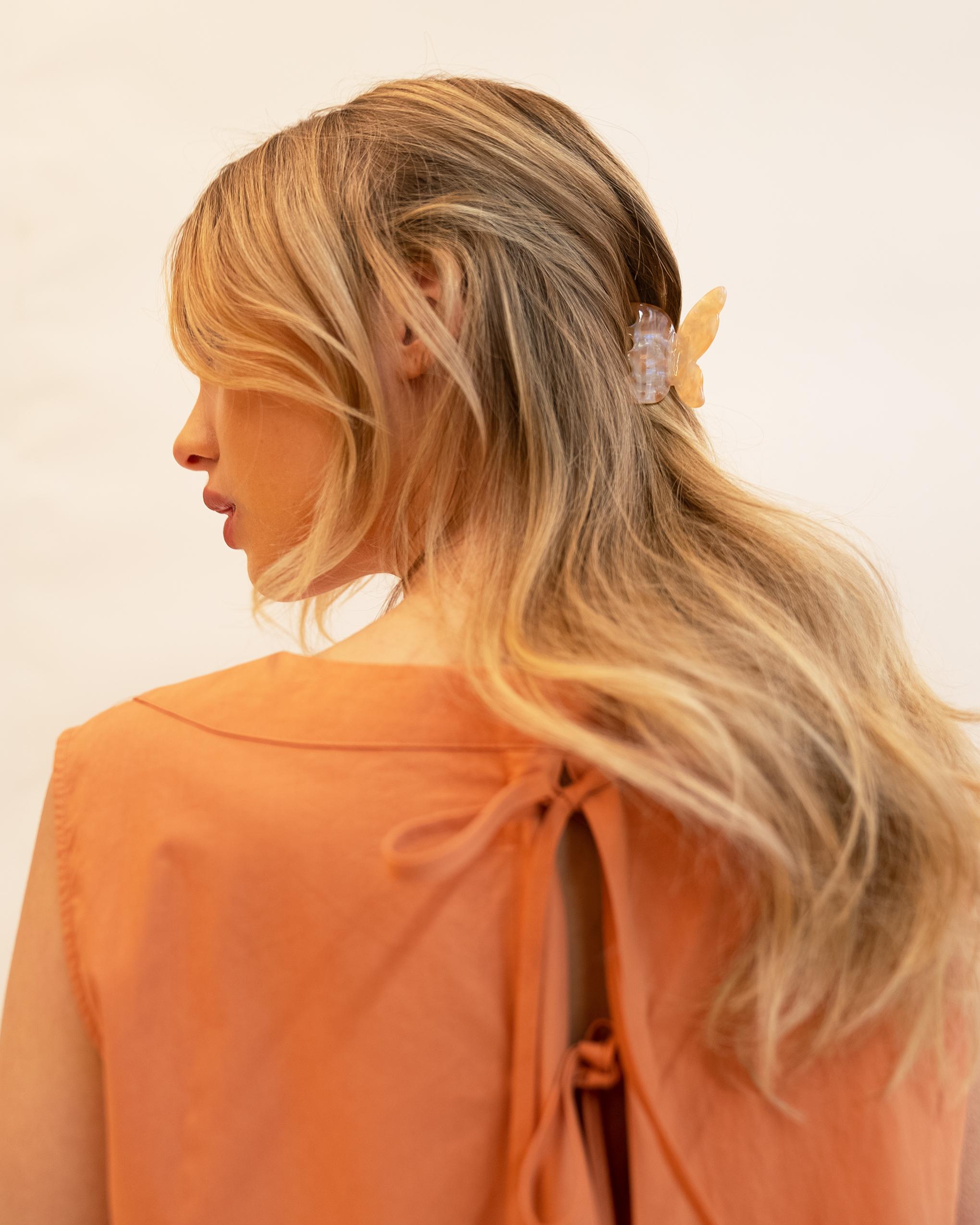 Model wearing Emin + Paul coral opal butterfly hair claw.