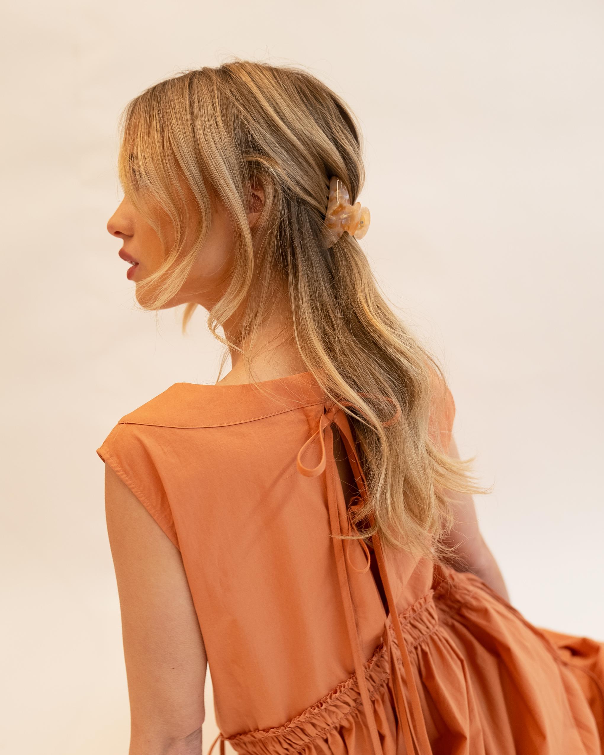 Model wearing Emin + Paul coral opal lattice hair claw.