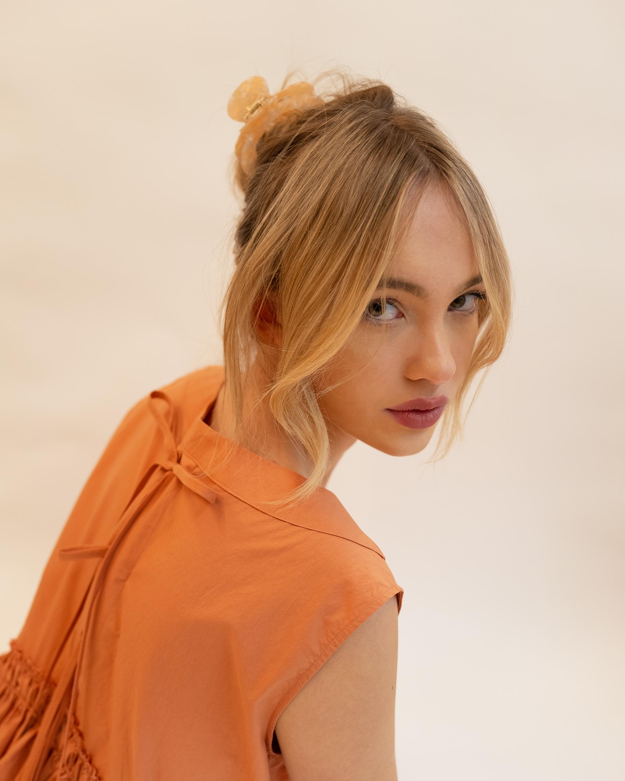 Model wearing Emin + Paul coral opal cut-out hair claw.