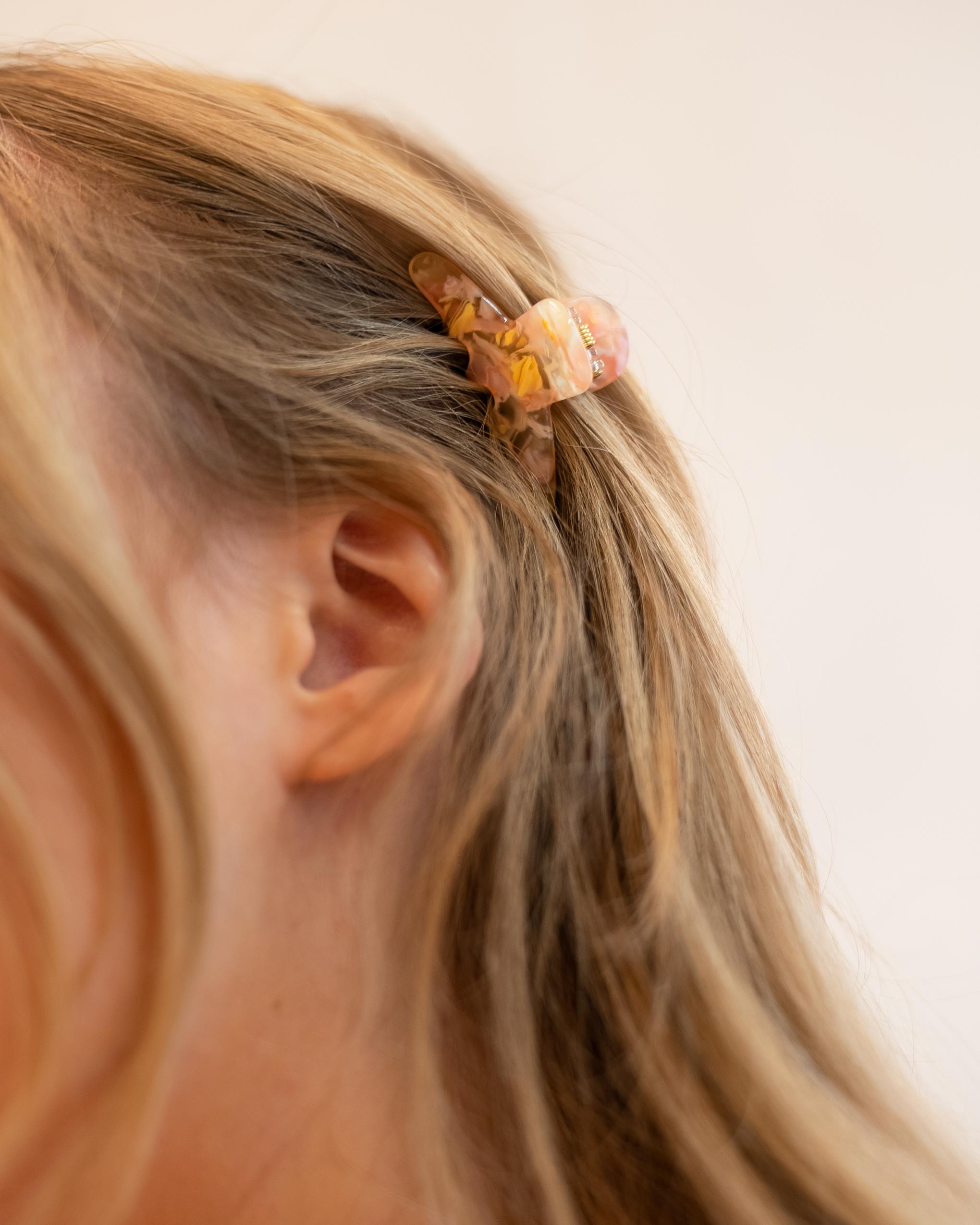 Model wearing Emin + Paul lemon blush mini curved hair claw.