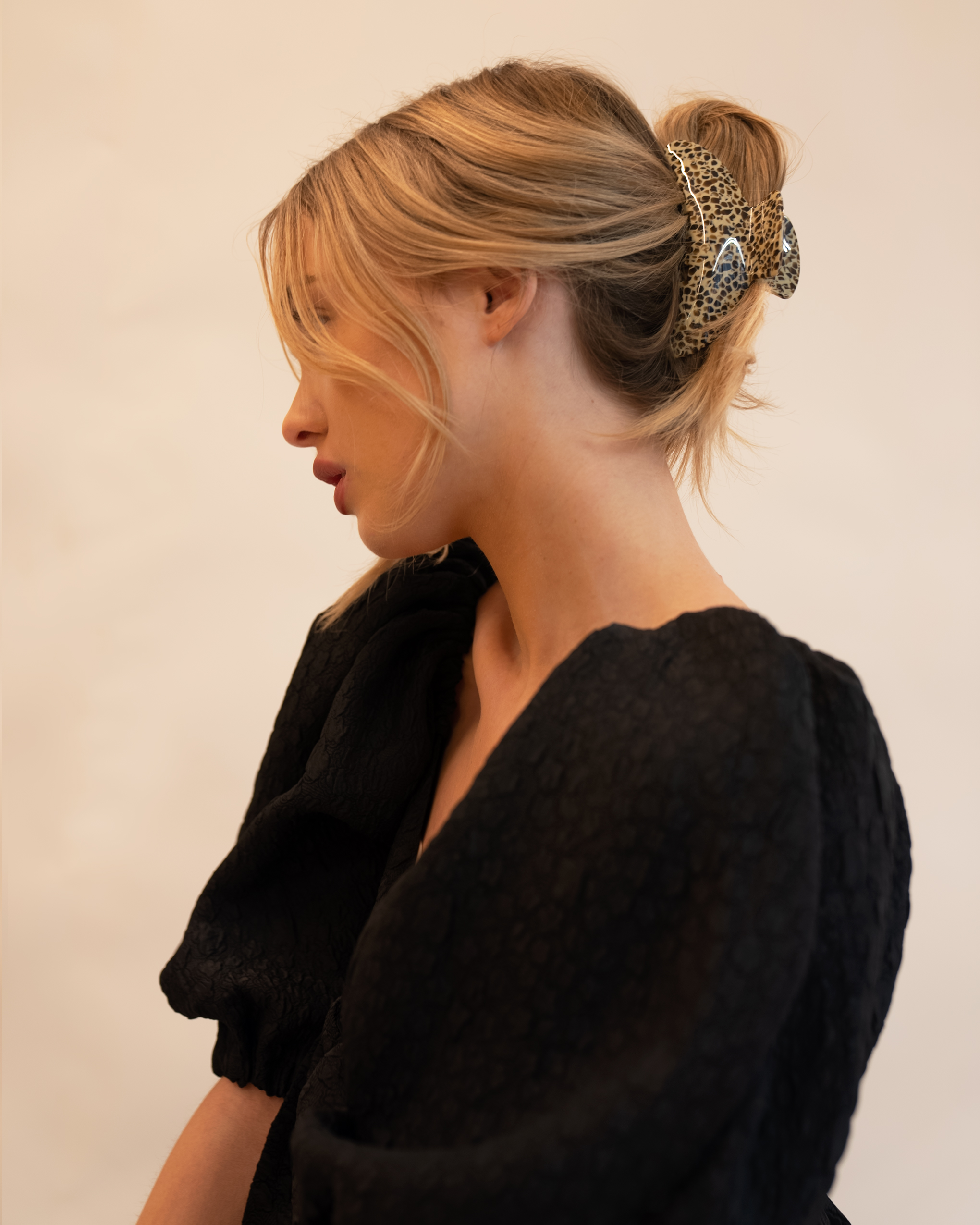 Model wearing Emin + Paul leopard chunky crescent hair claw.