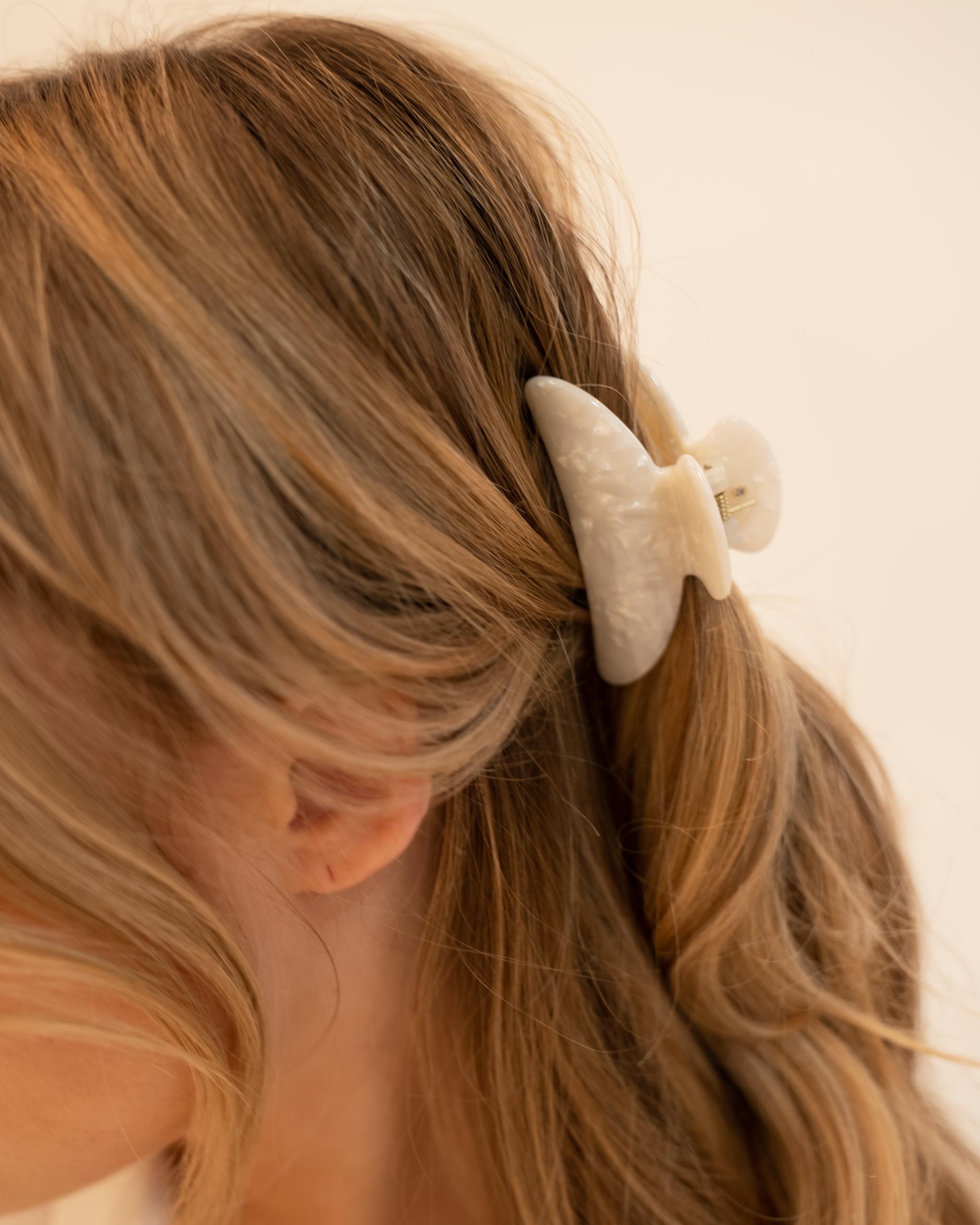 Model wearing Emin + Paul white opal crescent hair claw.