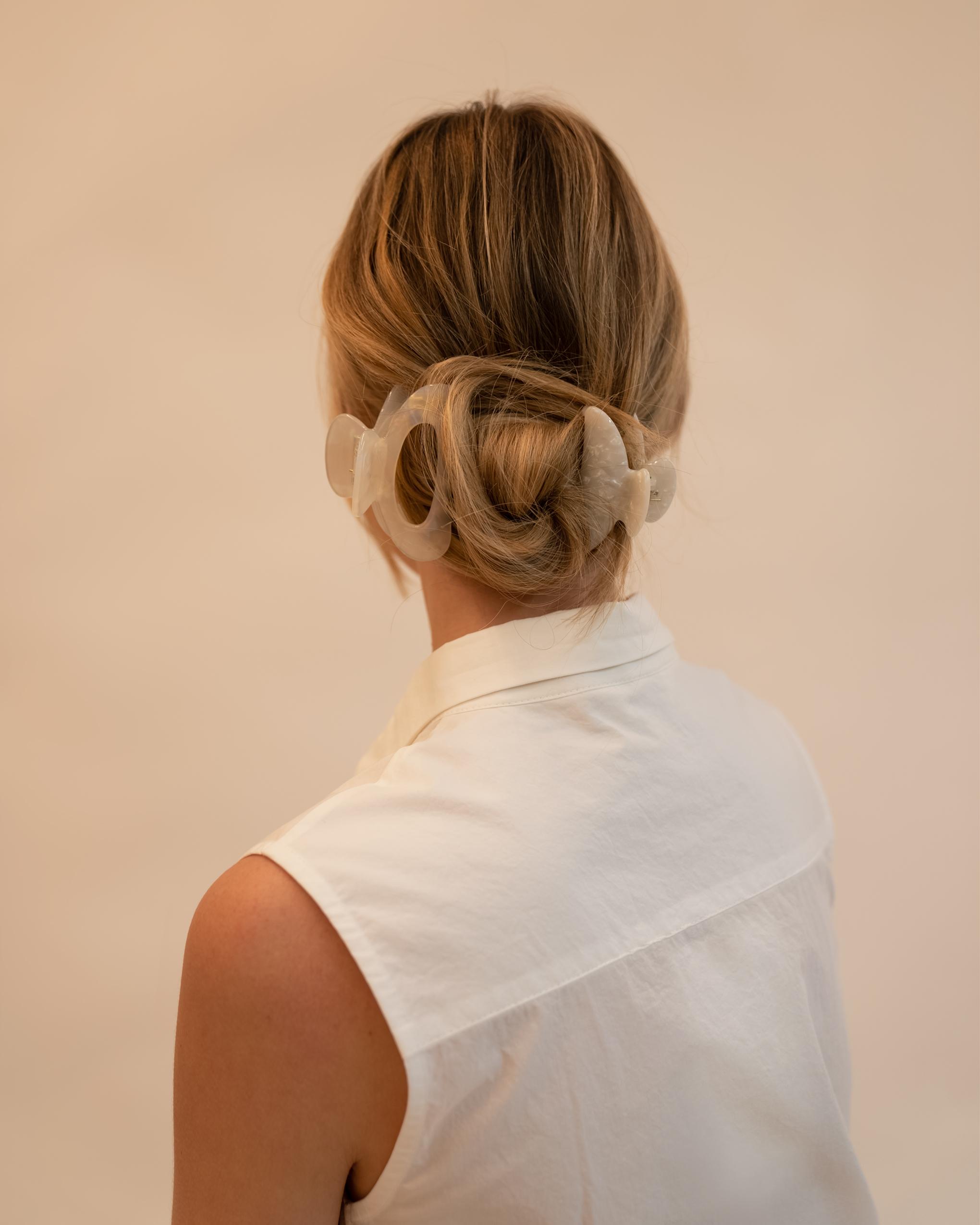 Model wearing Emin + Paul white opal cut out hair claw.