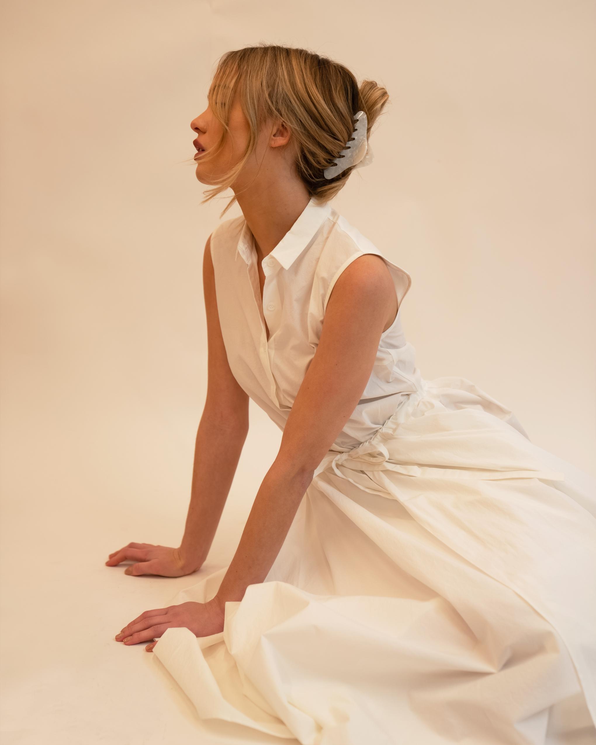 Model wearing Emin + Paul white opal twist hair claw.