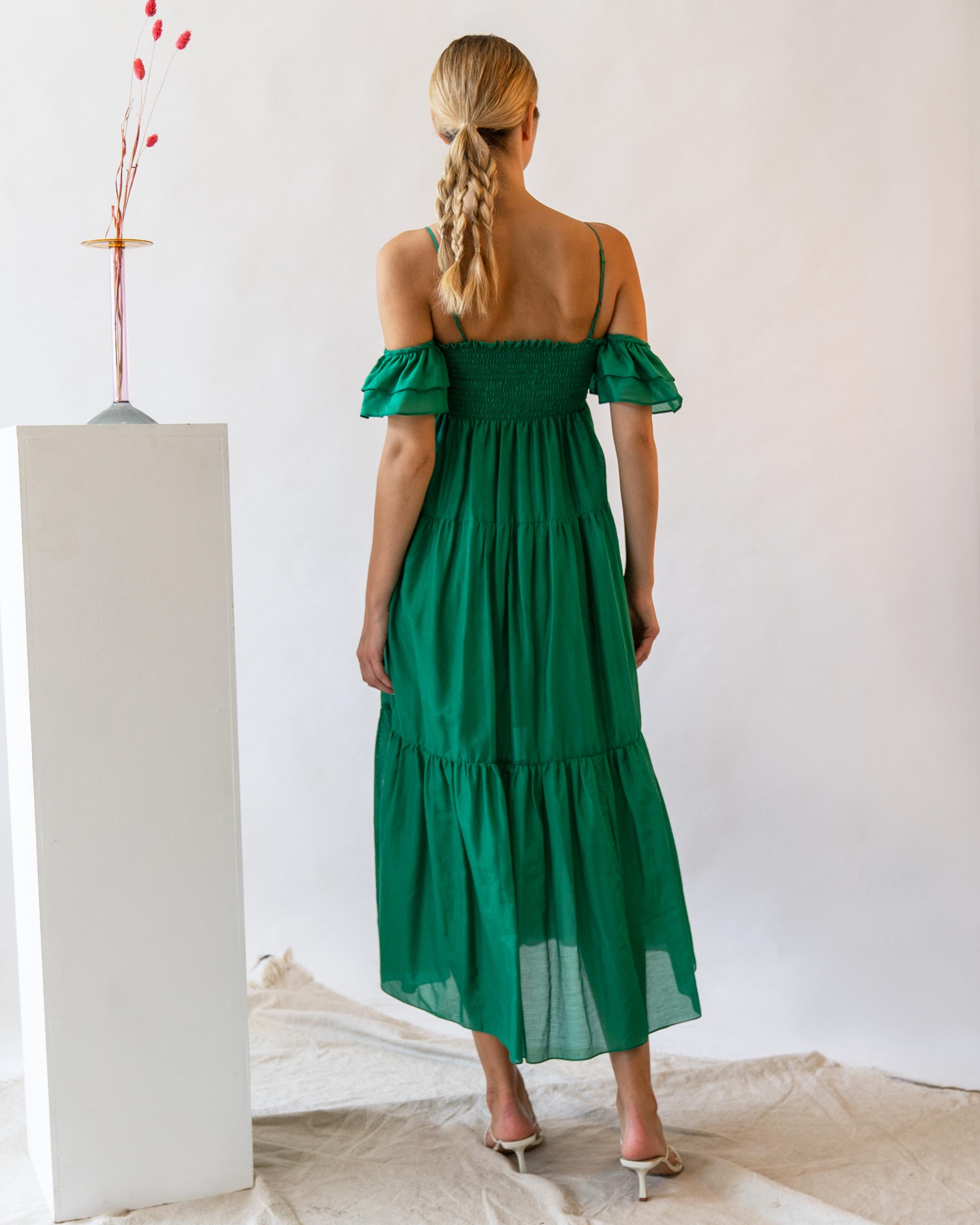 A woman is wearing green cotton-silk blend ruffle off-the-shoulder dress.