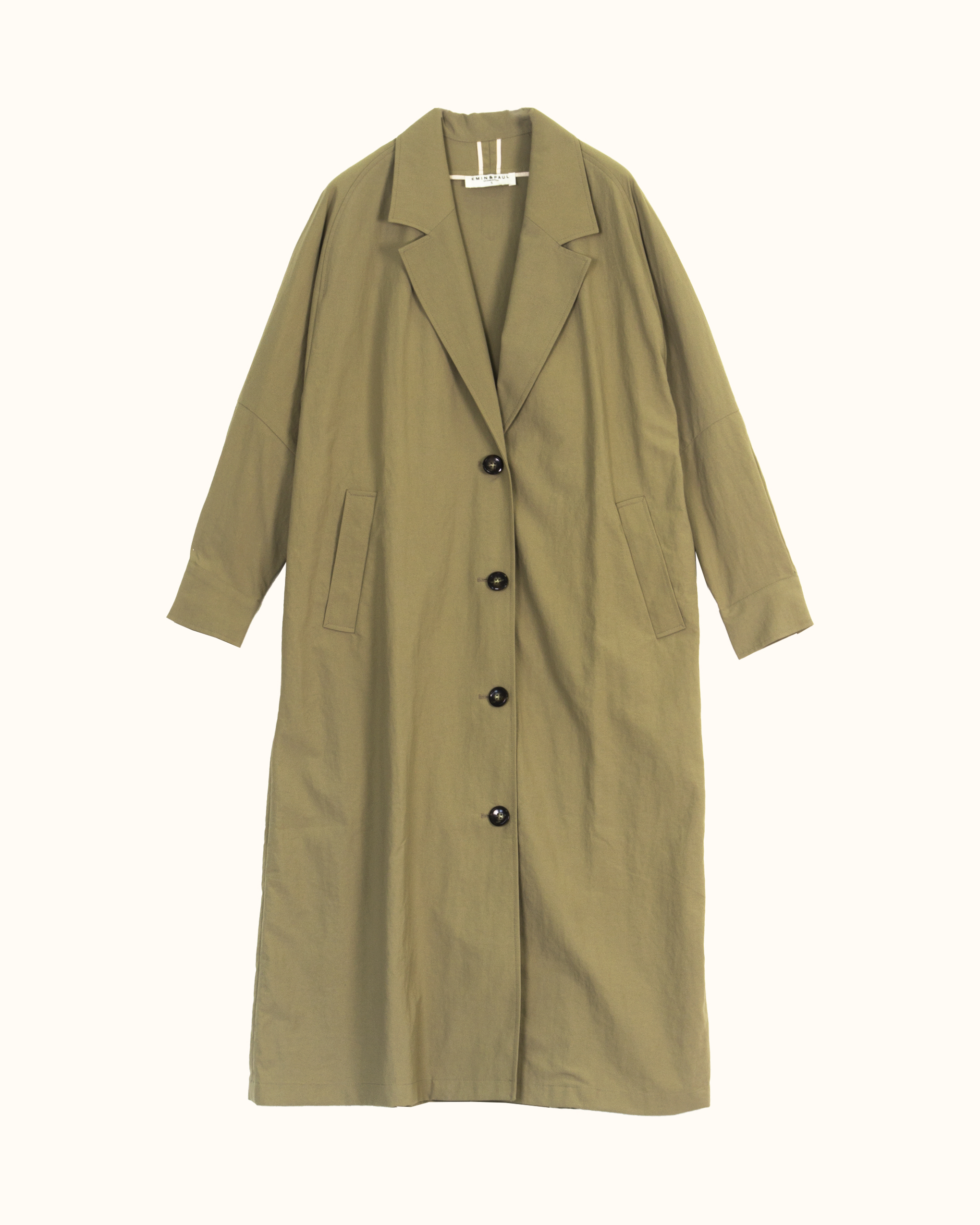 A woman is wearing Khaki volume sleeve cotton blend trench coat.