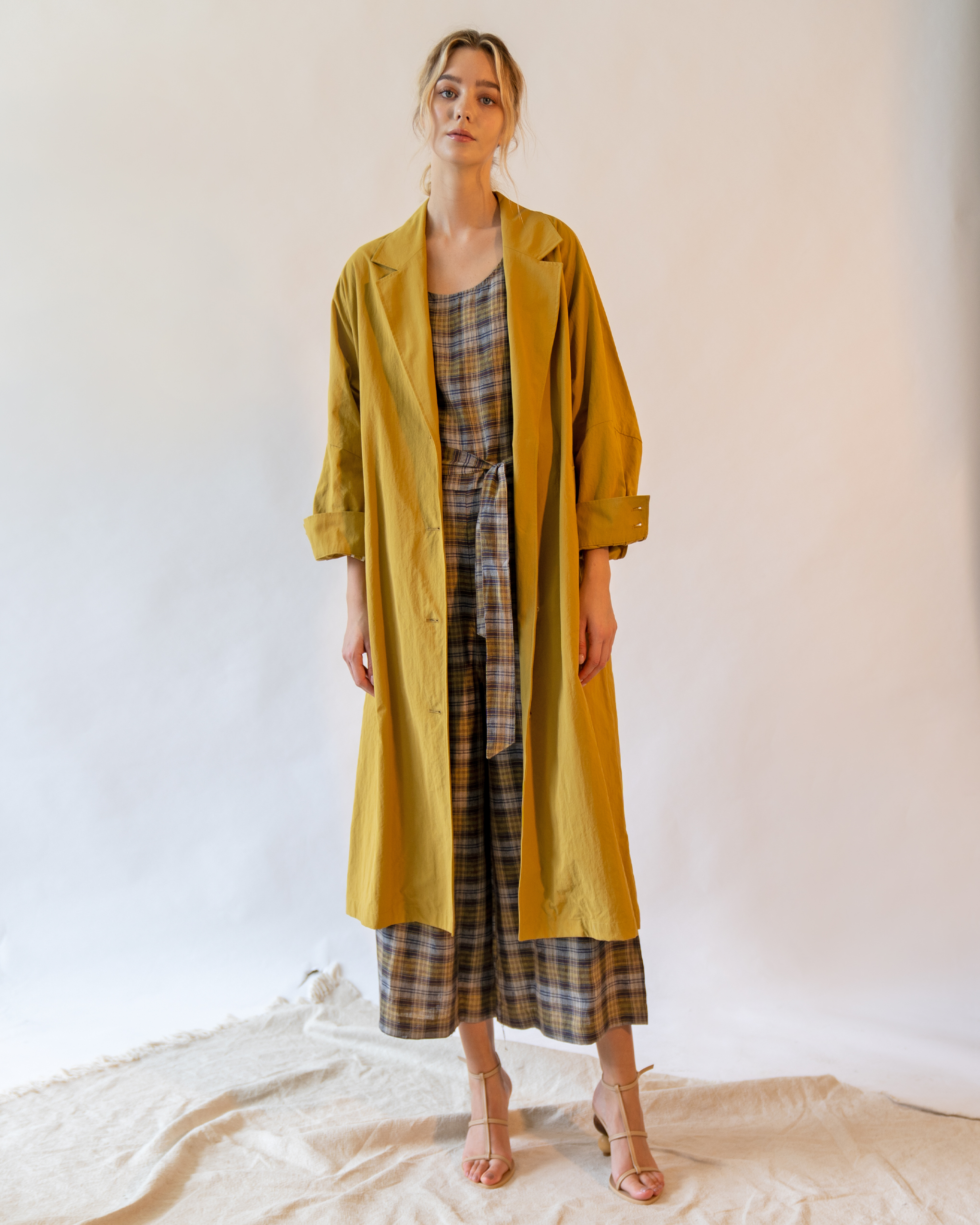 A woman is wearing mustard volume sleeve cotton blend trench coat.