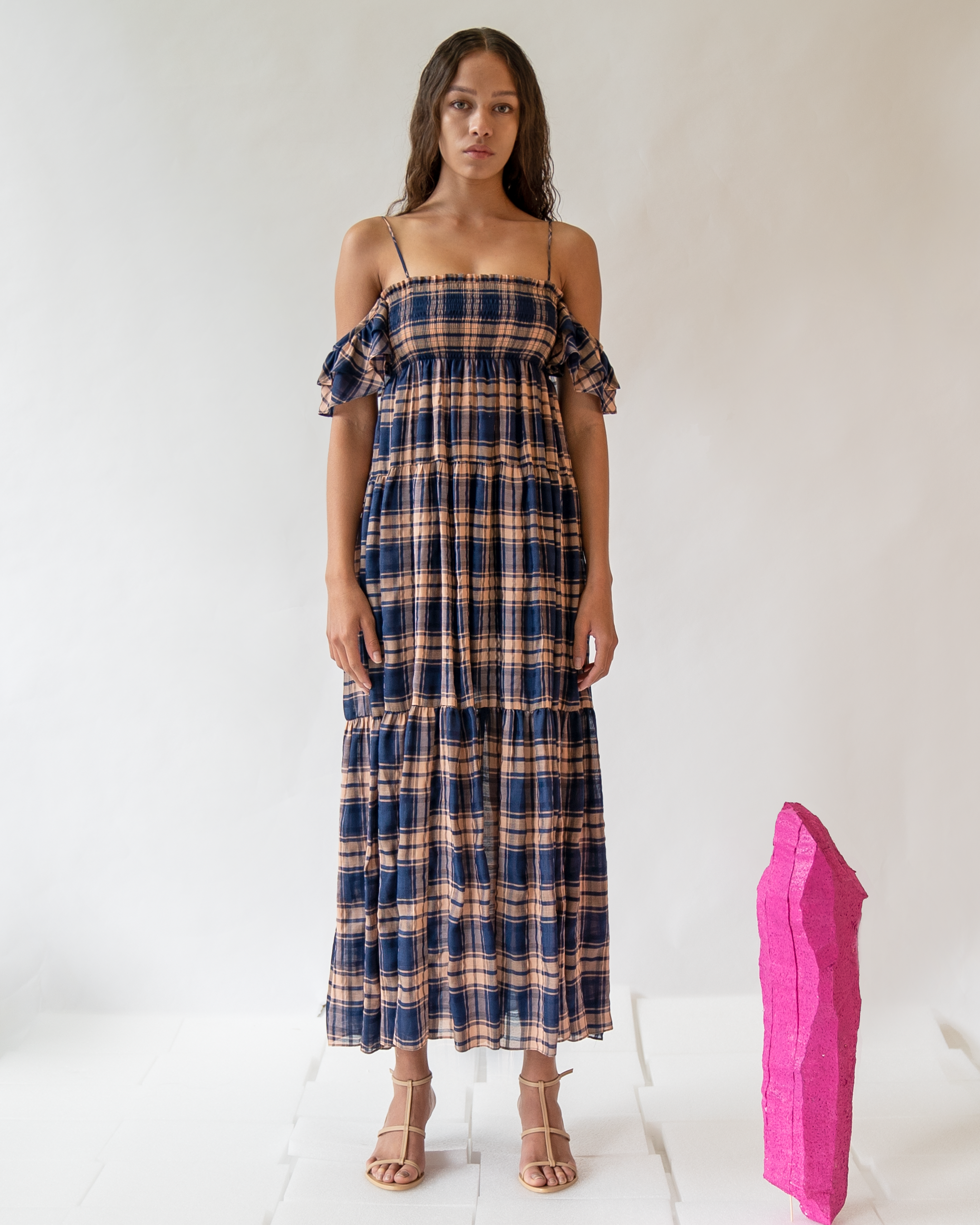 A woman is wearing navy-check pattern off-the-shoulder dress.