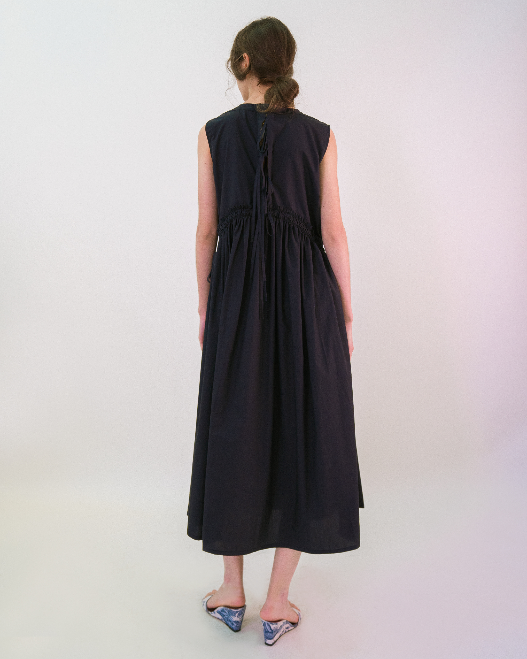 A woman is wearing a navy curved shirred waist side tie dress.