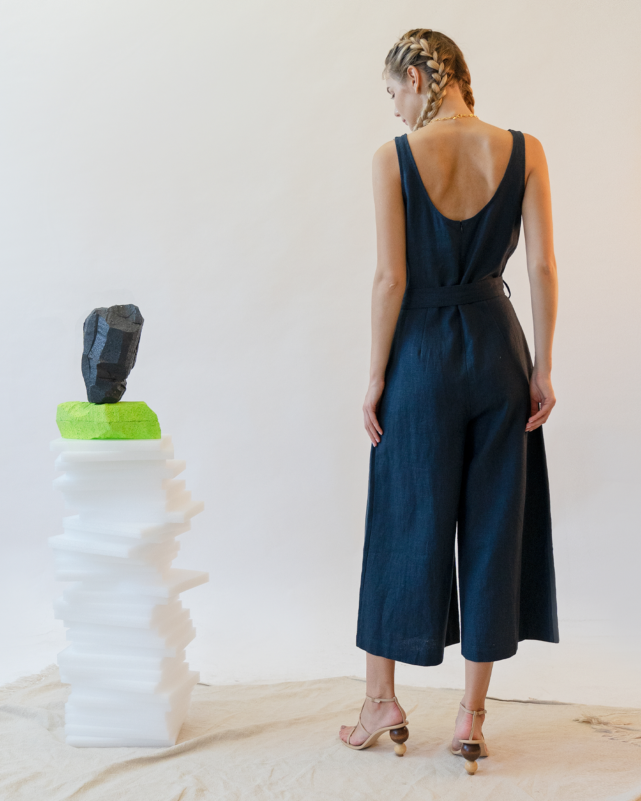 A woman is wearing a navy sleeveless scoop back linen jumpsuit.