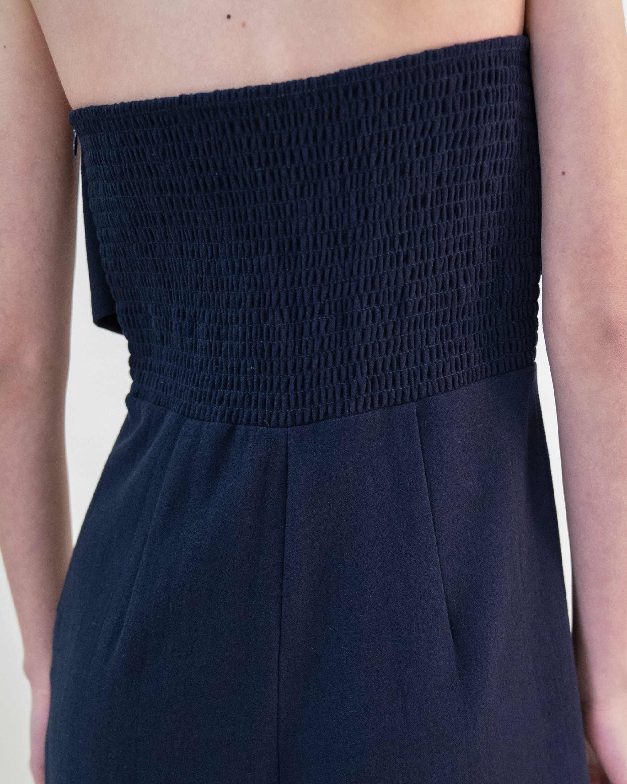 A woman is wearing a navy tie-front detail wide leg jumpsuit.