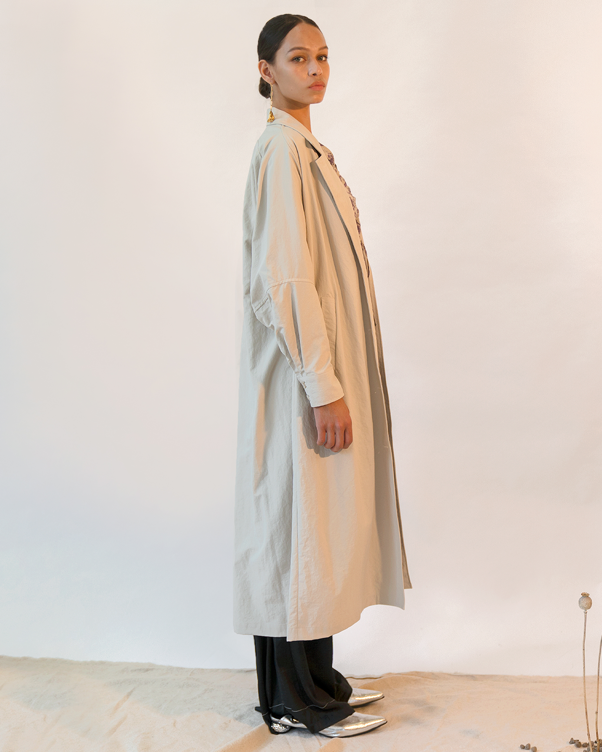 A woman is wearing an off-white oversized coat.