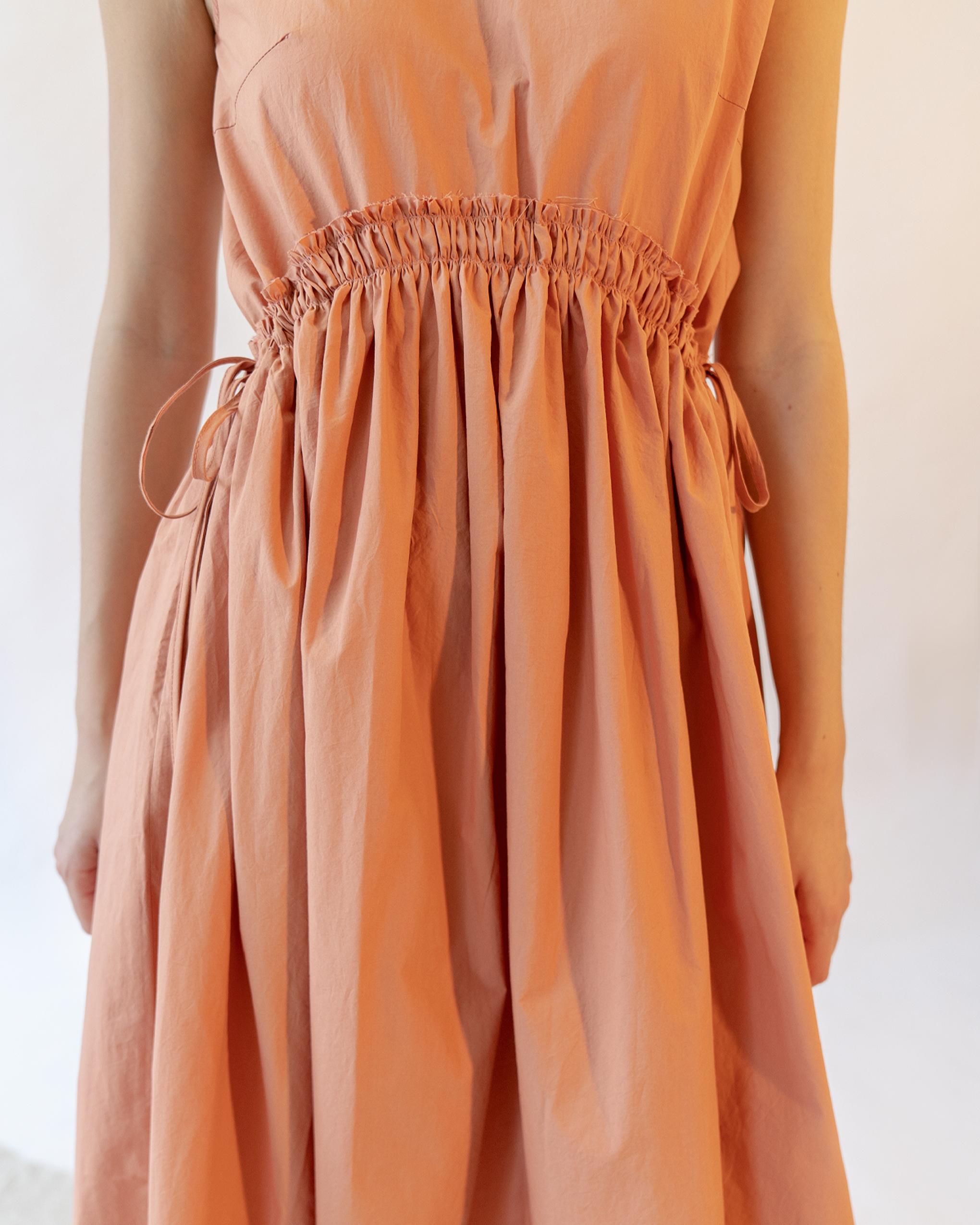 A woman is wearing an orange curved shirred waist side tie dress.