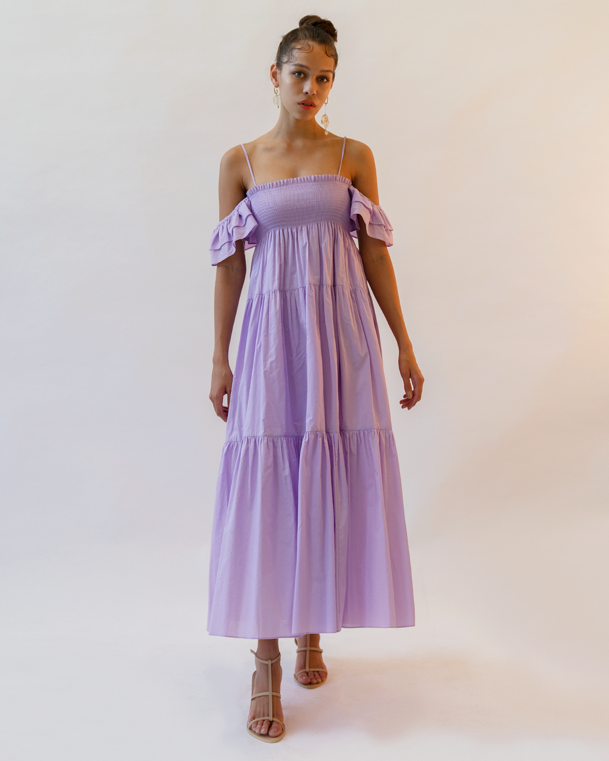 A woman is wearing violet off-the-shoulder dress.