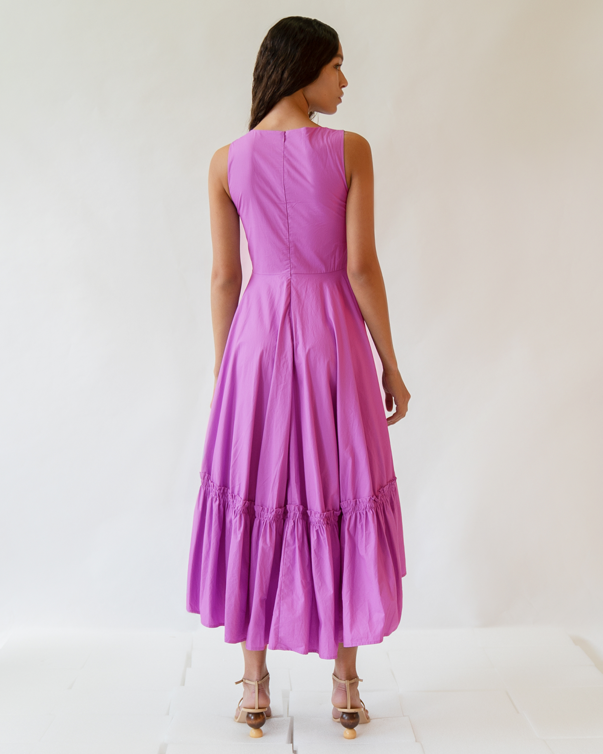 A woman is wearing a violet sleeveless curved gathered skirt cotton dress.