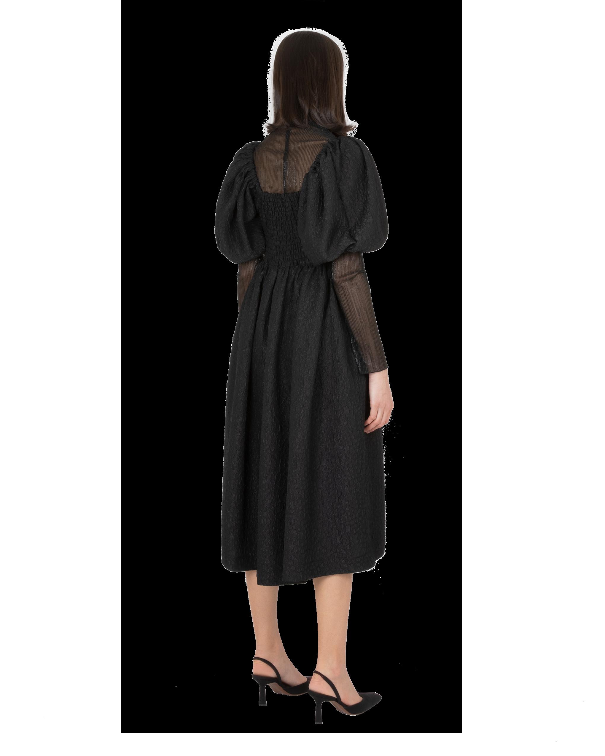 Model wearing EMIN + PAUL black puff sleeve dress.