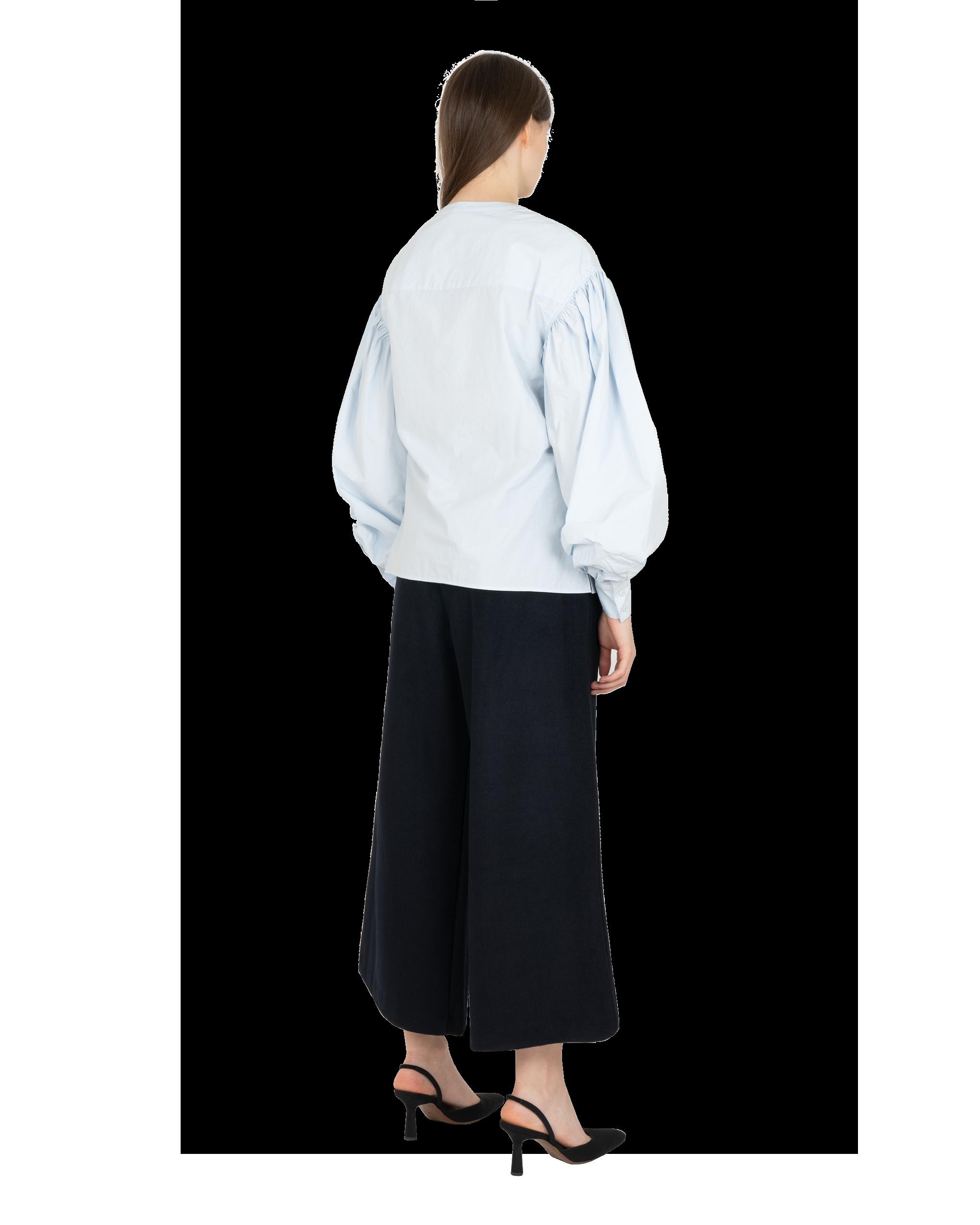 Model wearing EMIN + PAUL sky cinched illusion shirt.