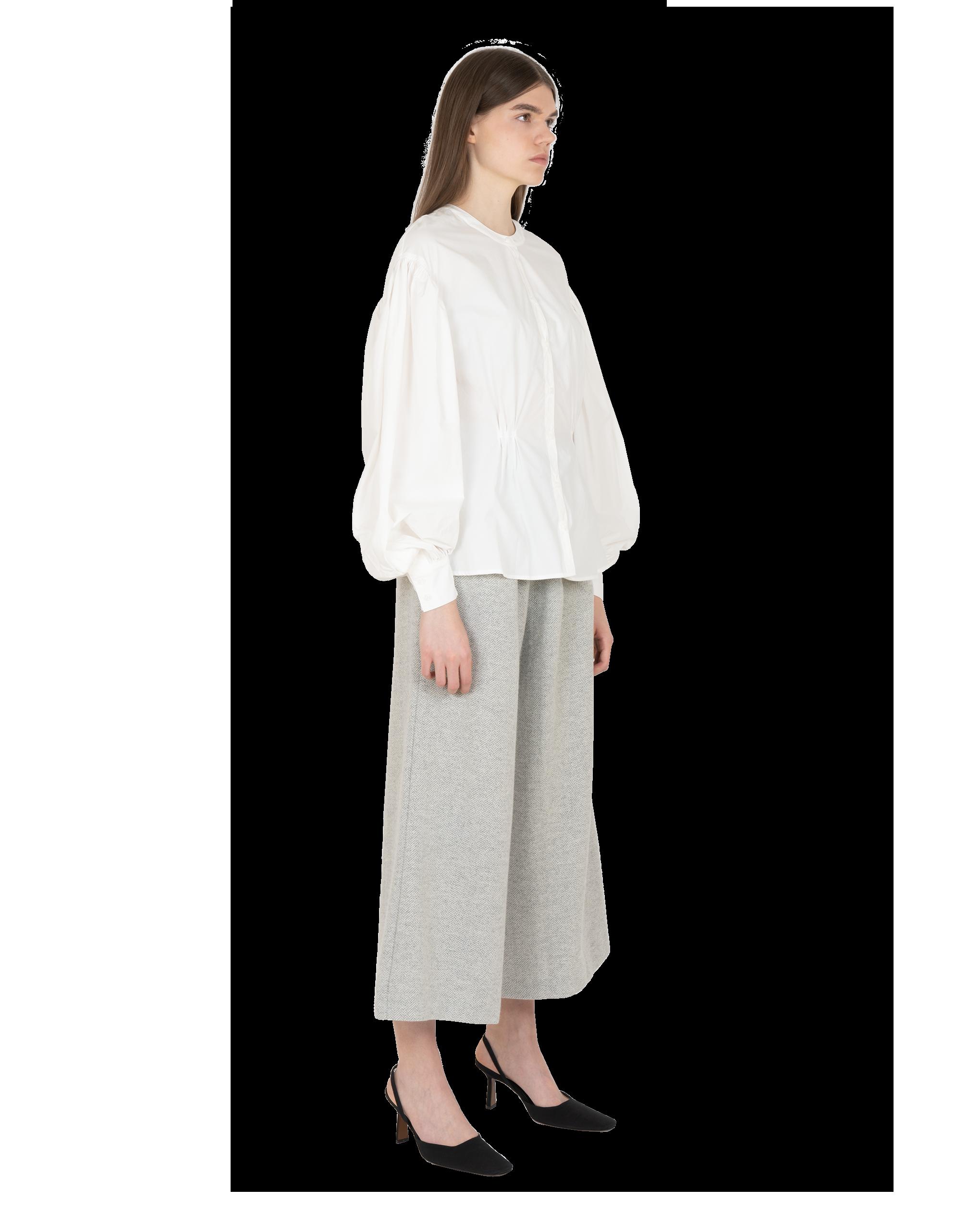 Model wearing EMIN + PAUL white cinched illusion shirt.